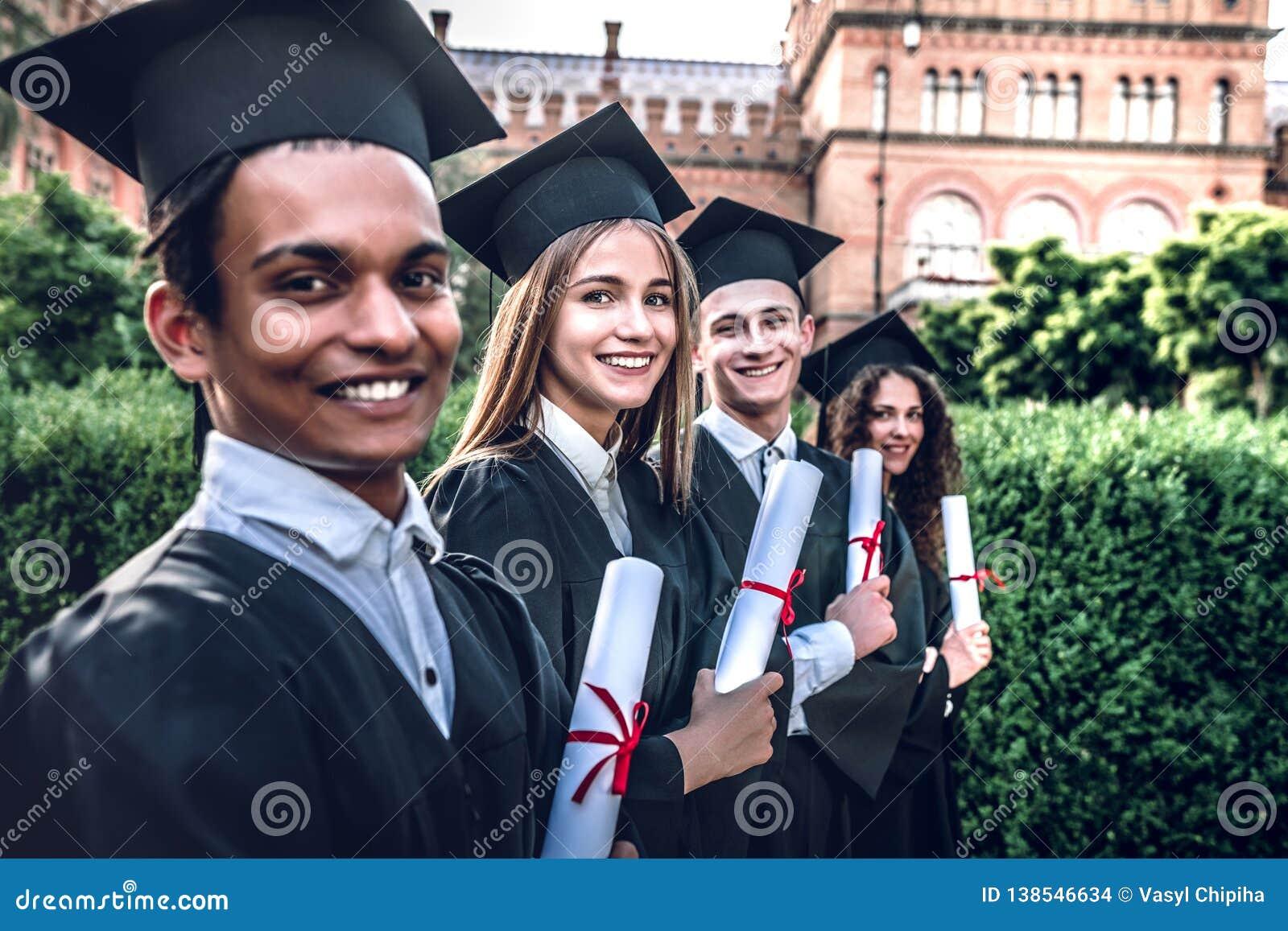 Kształcił i przygotowywa iść! Szczęśliwi absolwenci ono uśmiecha się stoją w uniwersytecki plenerowym w salopach z dyplomami w rę