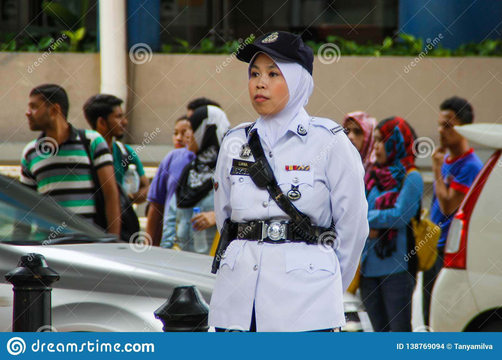 Asian police woman stands along the road in a white uniform, cap and hijab