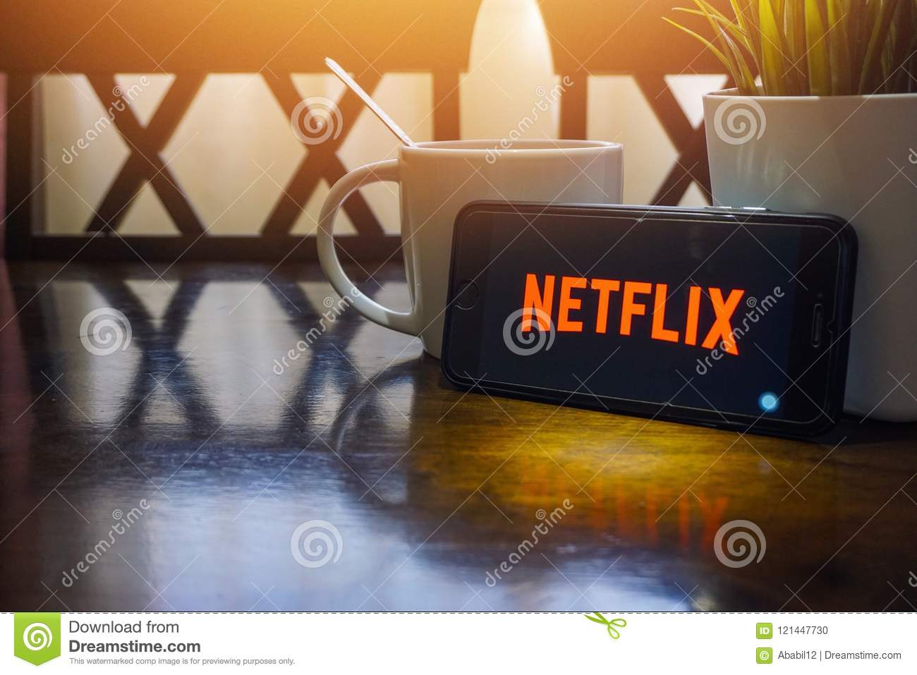 Smartphone displaying word Netflix on wooden table with selective focus and crop fragment