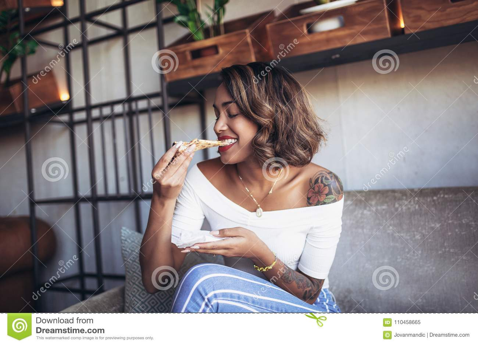 Kubansk kvinna som äter pizza i kafé