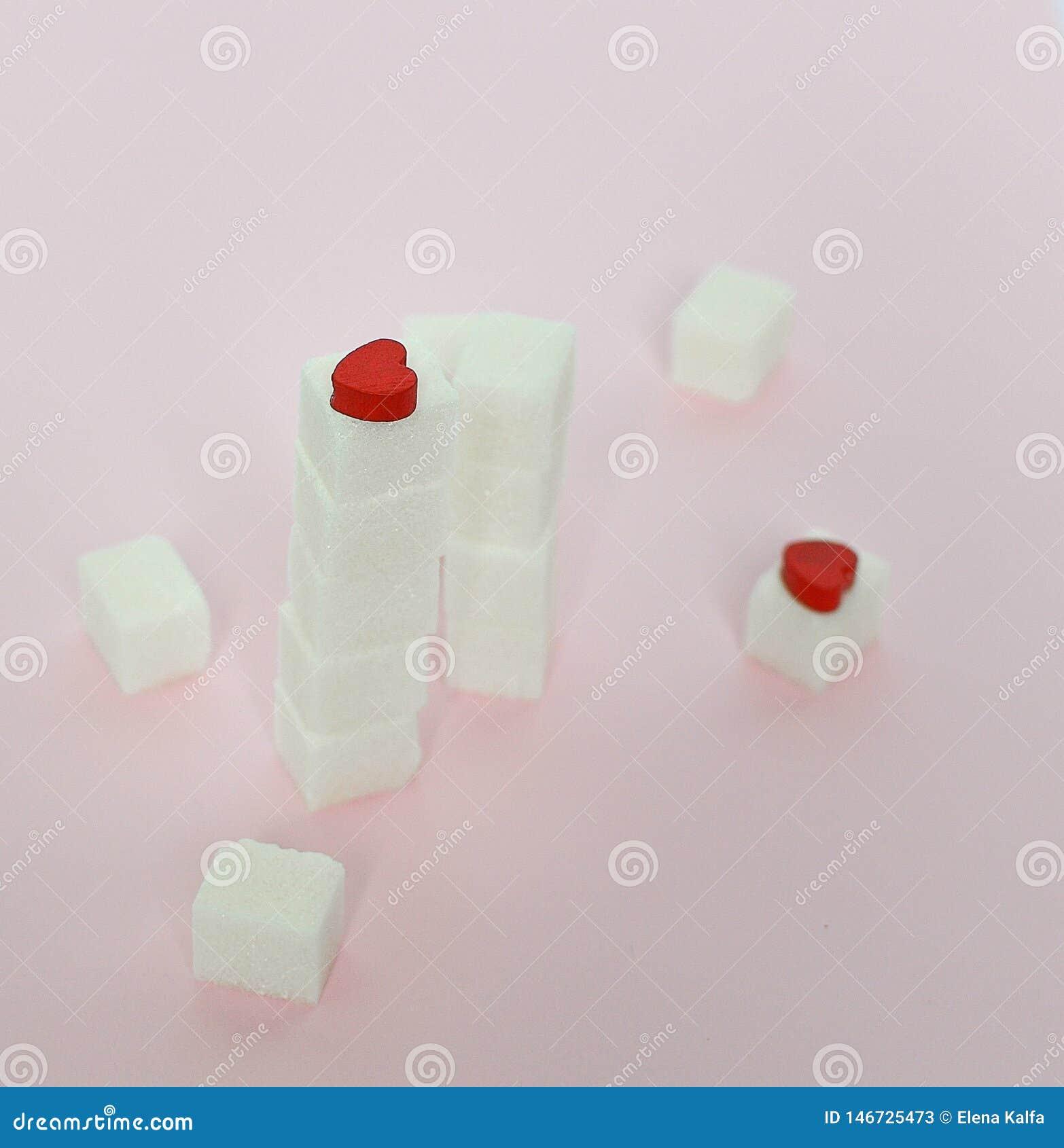Kuber för vitt socker på en rosa bakgrund Vad är begreppen av sockersjuka och kaloriintag begreppet av hjärtsjukdomen Ingen