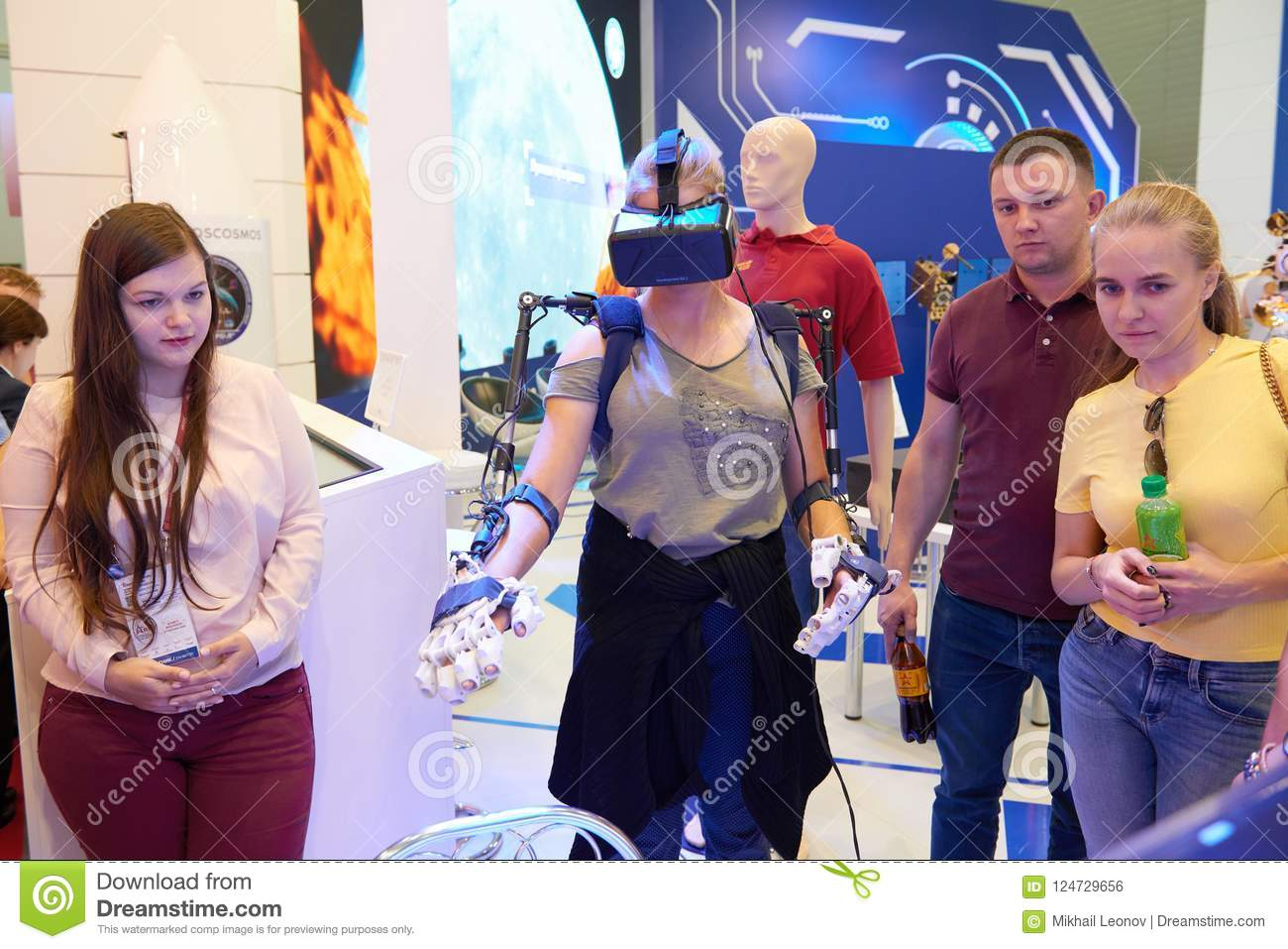 KUBINKA, RUSSIA, AUG.24, 2018: Young girl in exosuit and virtual reality glasses is trying to operate space robot on a computer si
