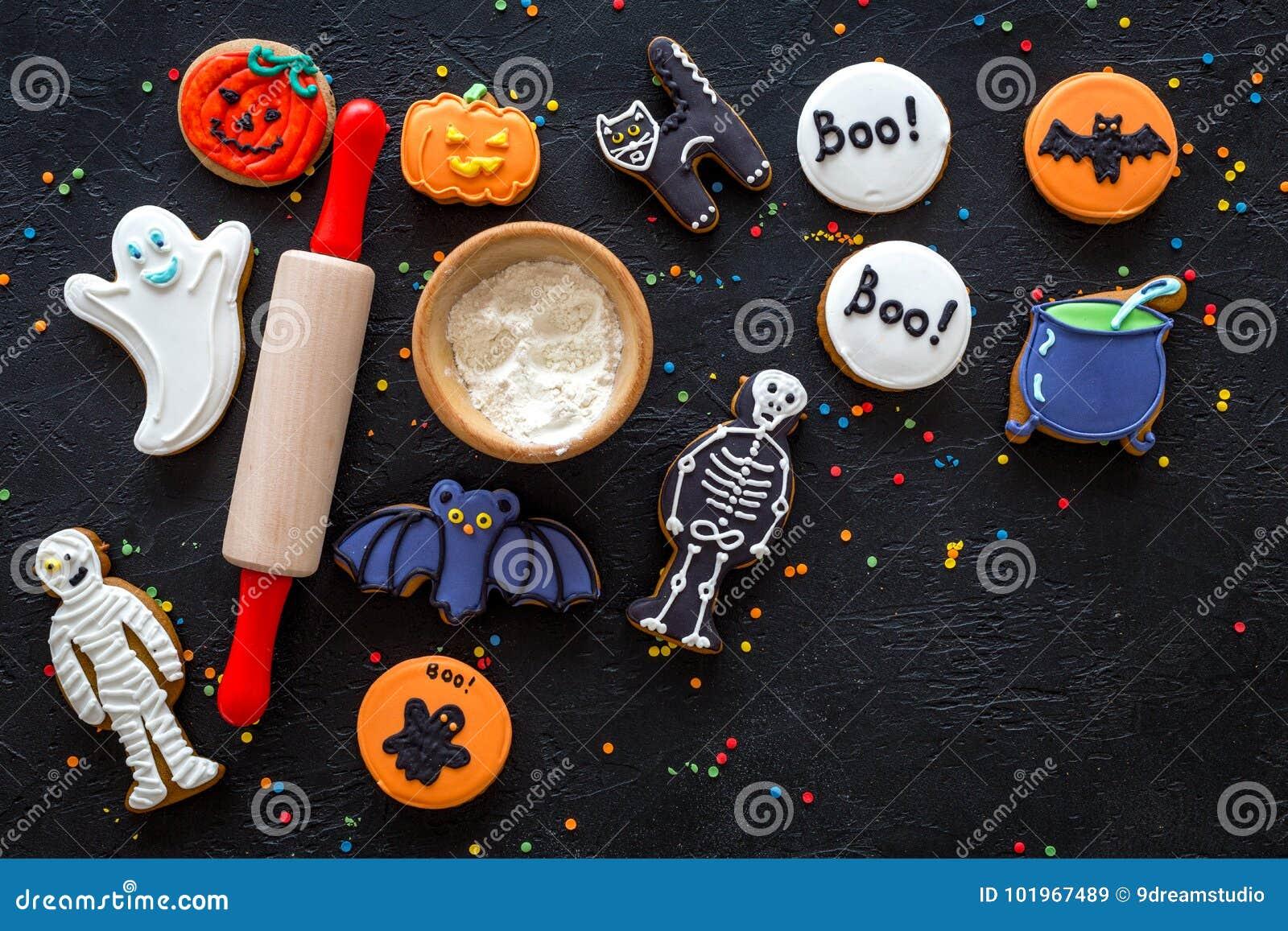 Kucbarscy Halloween piernikowi ciastka uderzają, kościec, duchów cukierki blisko tocznej szpilki na czarnym tło odgórnego widoku
