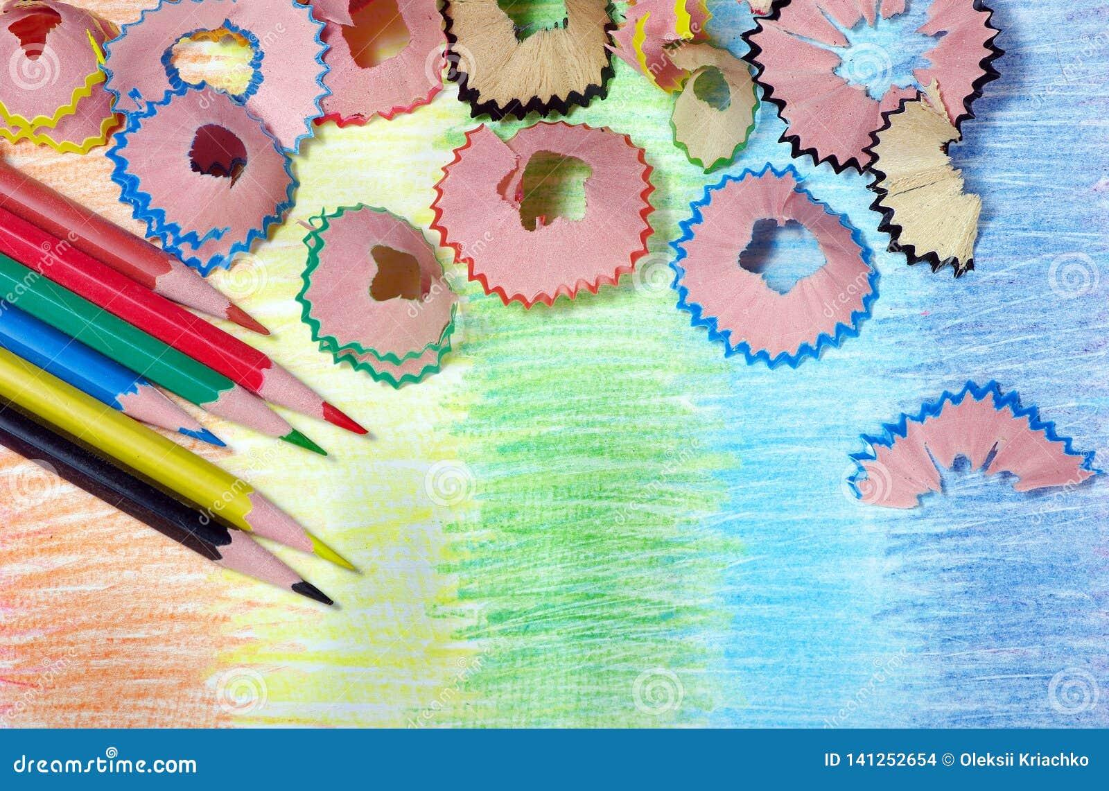 Kulöra blyertspennashavings blyertspennor på en regnbågebakgrund Färger av regnbågen