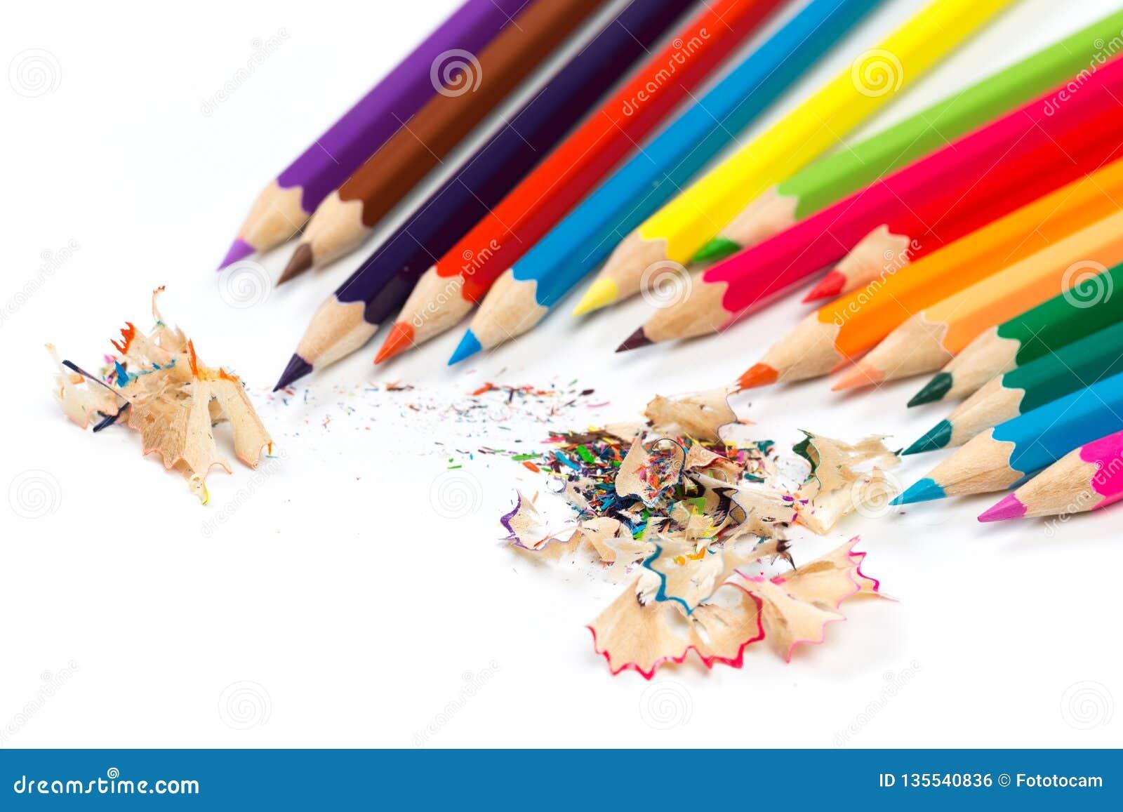 Kulöra blyertspennor och shavings med blyertspennor Vässare av blyertspennor på en vit bakgrund