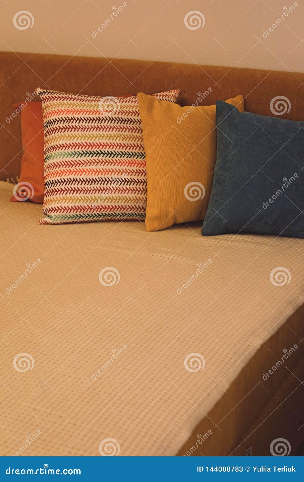 Kul?ra kuddar och med modellen i en remsa av kuddar p? s?ng Inre av det moderna sovrummet med hemtrevlig s?ng Vila och att sova,