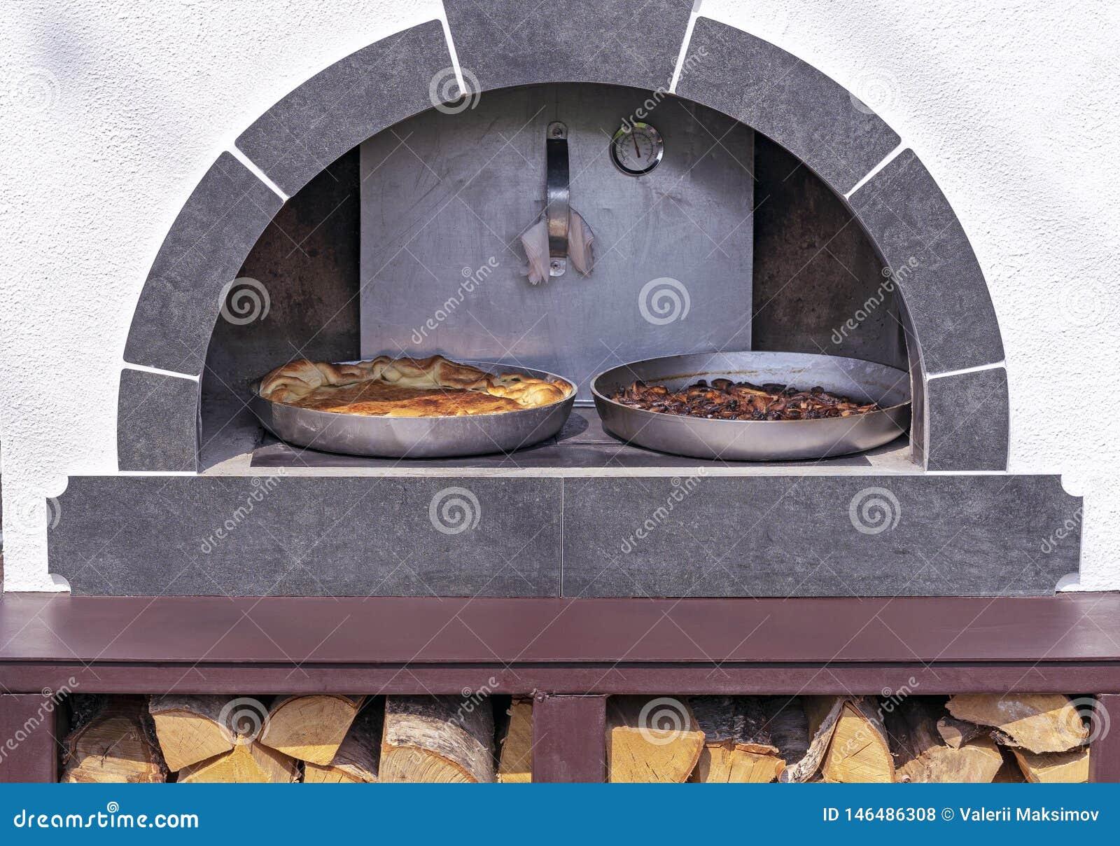 Kulebiaki gotują w starym Rosyjskim piekarniku Rosyjska drewniana kuchenka