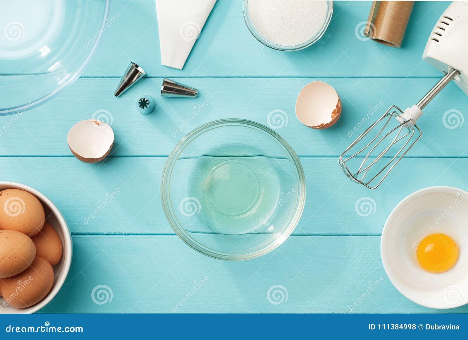 Kulinarisk bakgrund med avskilda äggvitor och äggulor i bunkarna på den blåa trätabellen