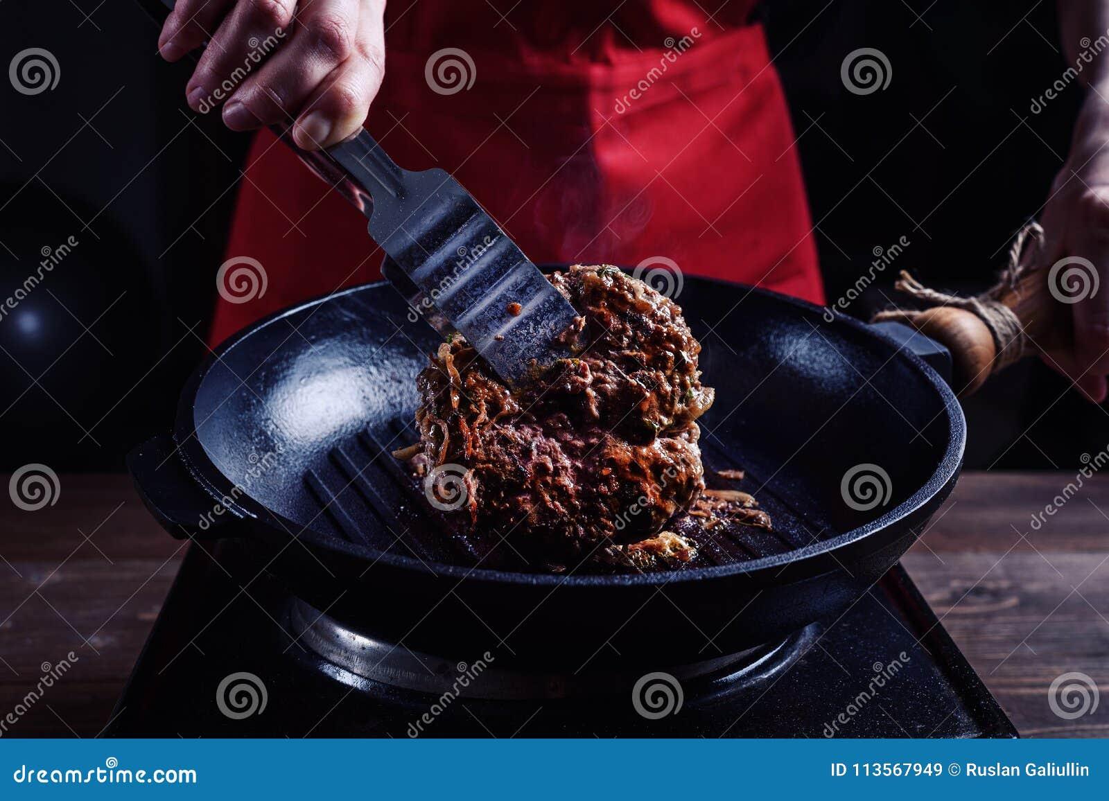 Kulinarny wołowina stek na grill niecce w domu Kobieta w czerwonym fartuchu podrzuca smażącego kawałek mięso
