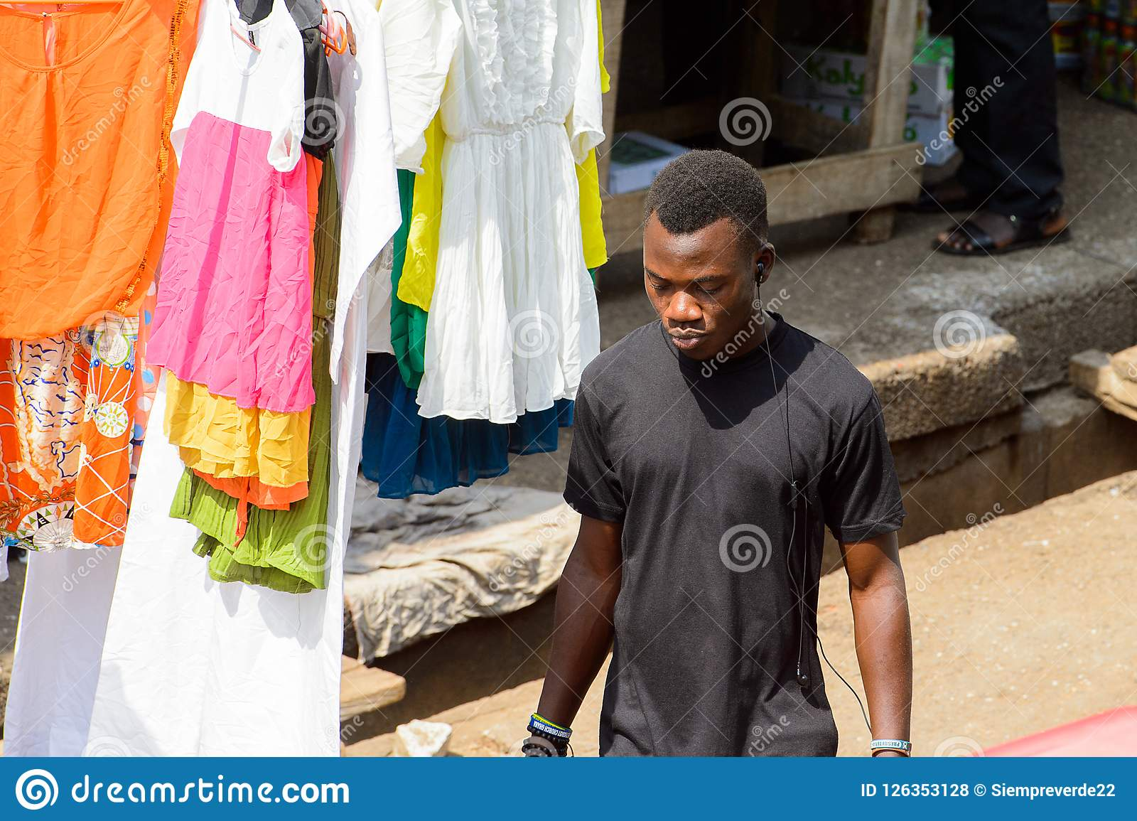 Unidentified Ghanaian Man In Black Shirt Listens To Music