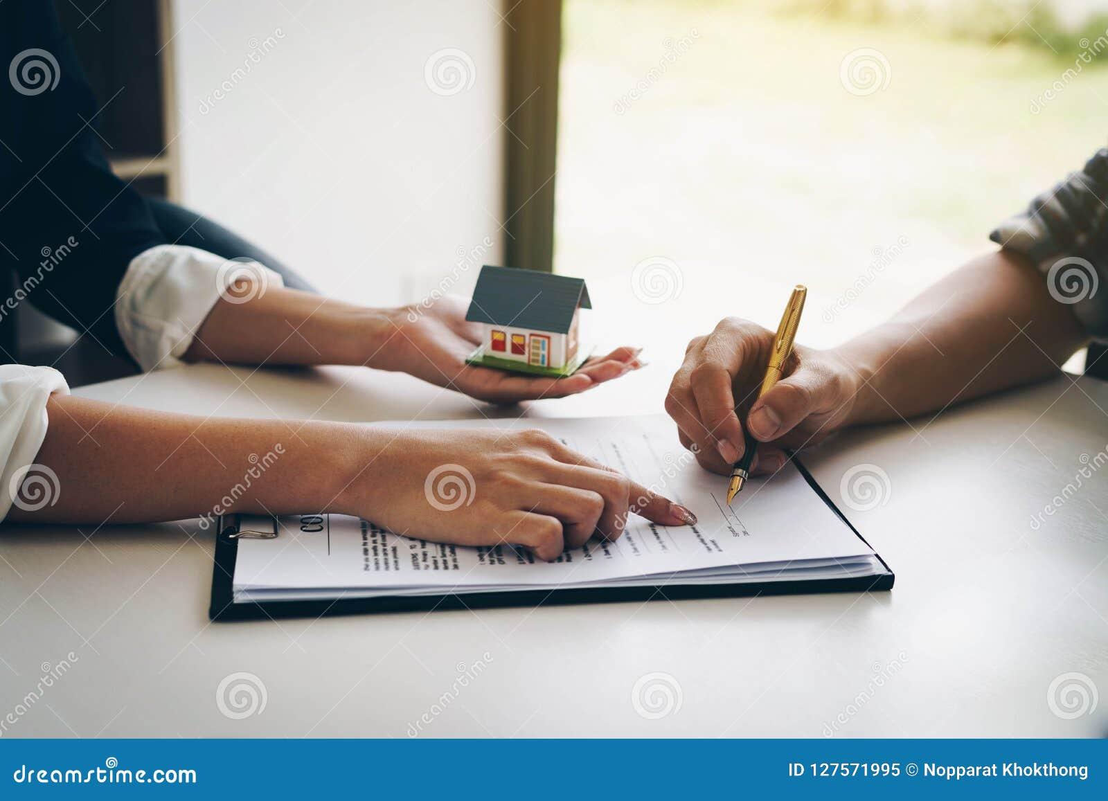 Kund som undertecknar ett pappers- dokument för köpande hus Lyckliga indiska tangenter för visning för affärskvinna eller fastigh