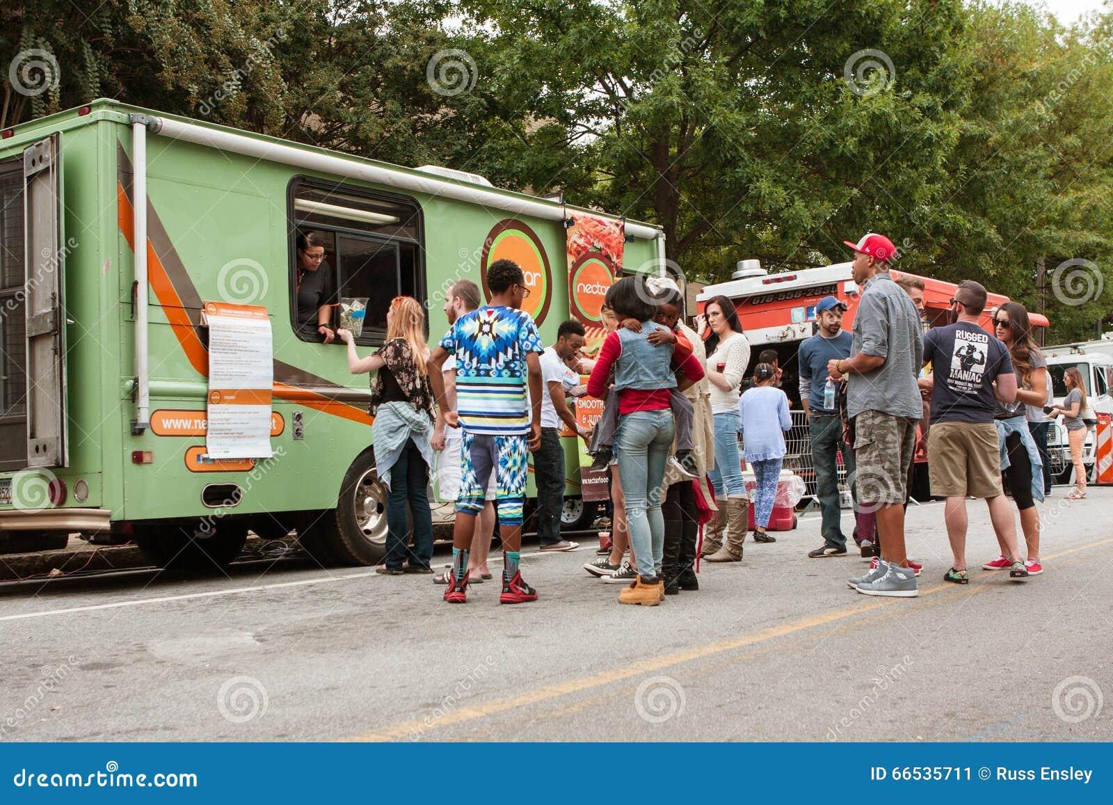 Kunden-Stand in der Linie, zum von Mahlzeiten von den Lebensmittel-LKWs zu kaufen