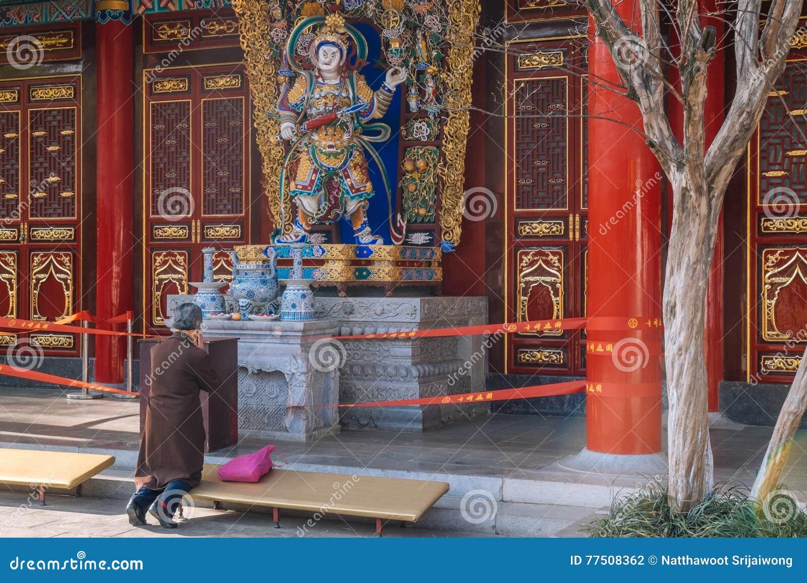 KUNMING 13 DE MARZO DE 2016 La mujer mayor está rogando en el templo budista de Yuantong,