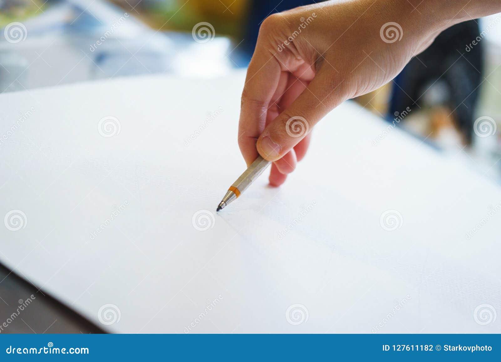 Kunstenaar met een potloodclose-up terwijl het trekken van een schets op schoon document