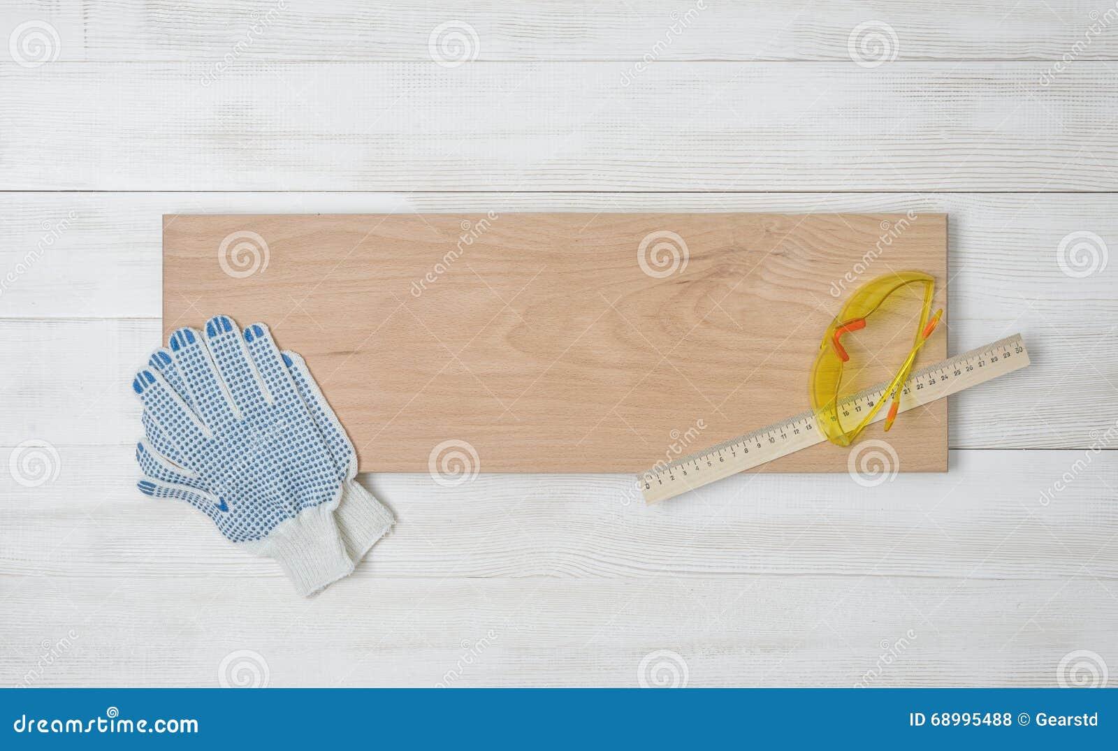Kunstzusammensetzungsaufmachung von den Handschuhen, von Gläsern, von Zentimetermachthaber und von beige hölzerner Planke, die au