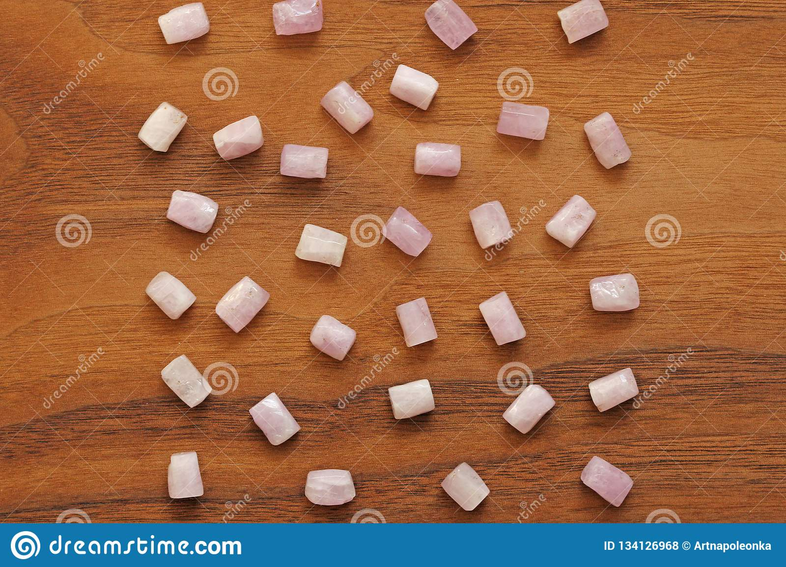 Kunzite is a natural pink stone for creating Jewelry on a natural wooden background. Natural crystals of pink and lilac stones