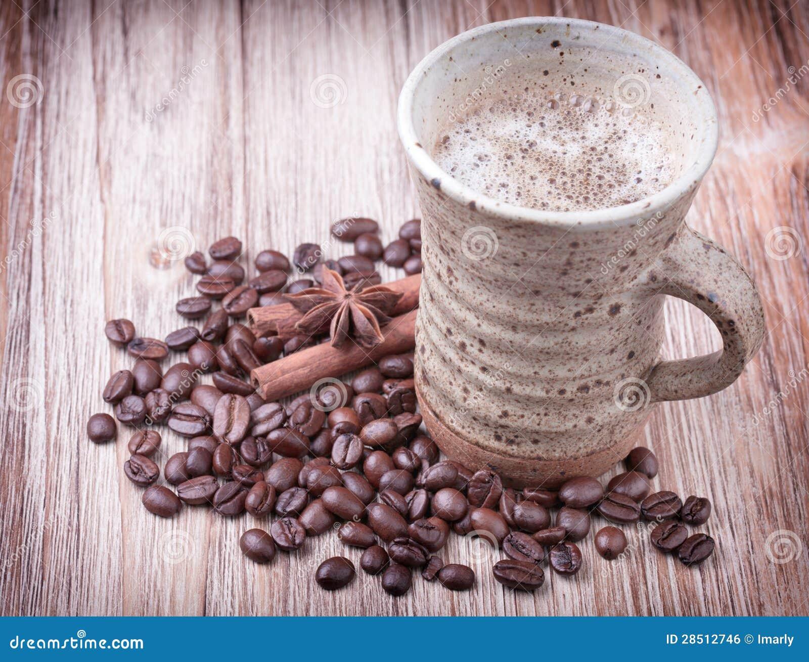 Kupa av svart kaffe, kanel, anis och grillade kaffebönor