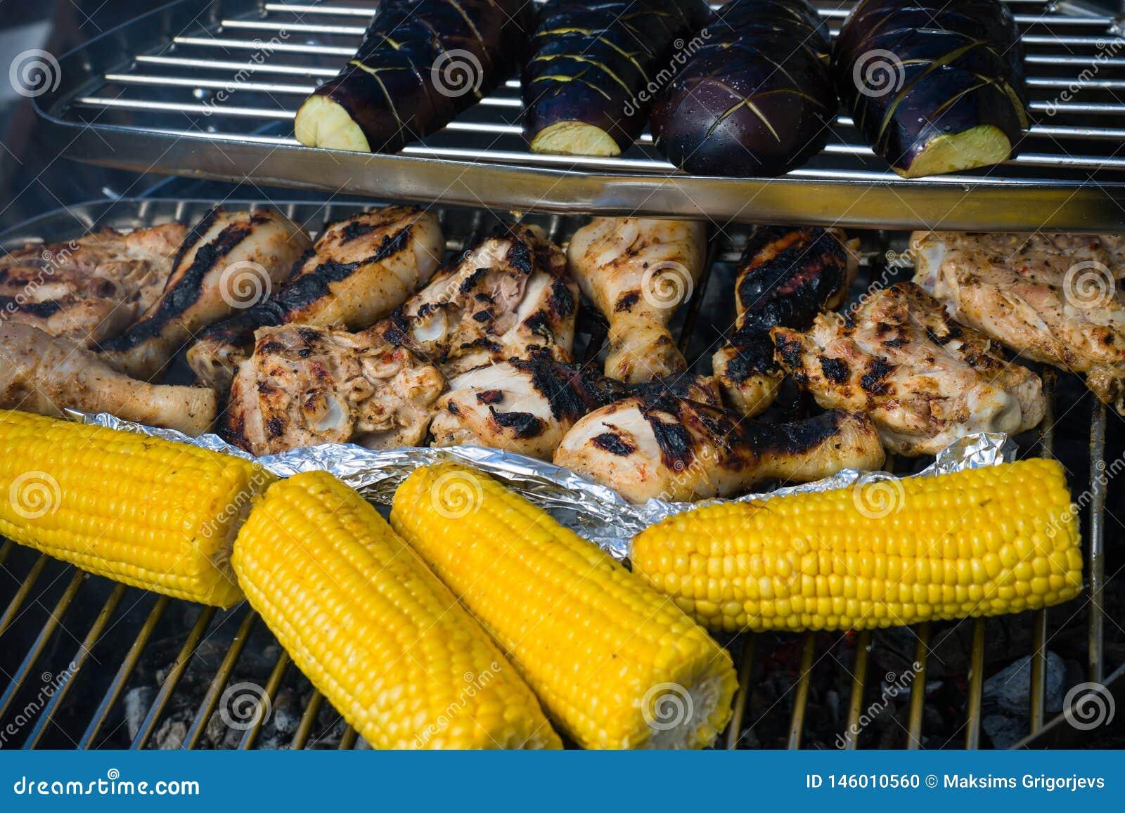 Kurczaków drumsticks z warzywami: słodka kukurudza i aubergines na grillu piec na grillu z ogieniem