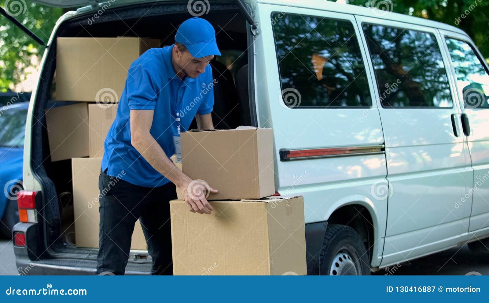 Kurier bierze pudełka out od doręczeniowego samochodu dostawczego, poruszająca firma, towarowy transport