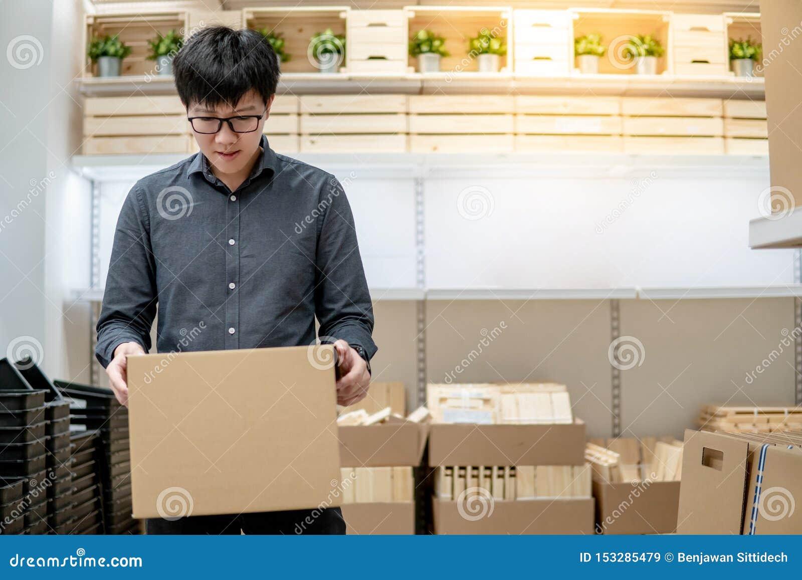 Kuriera mężczyzny przewożenia pudełka zakupy w magazynie