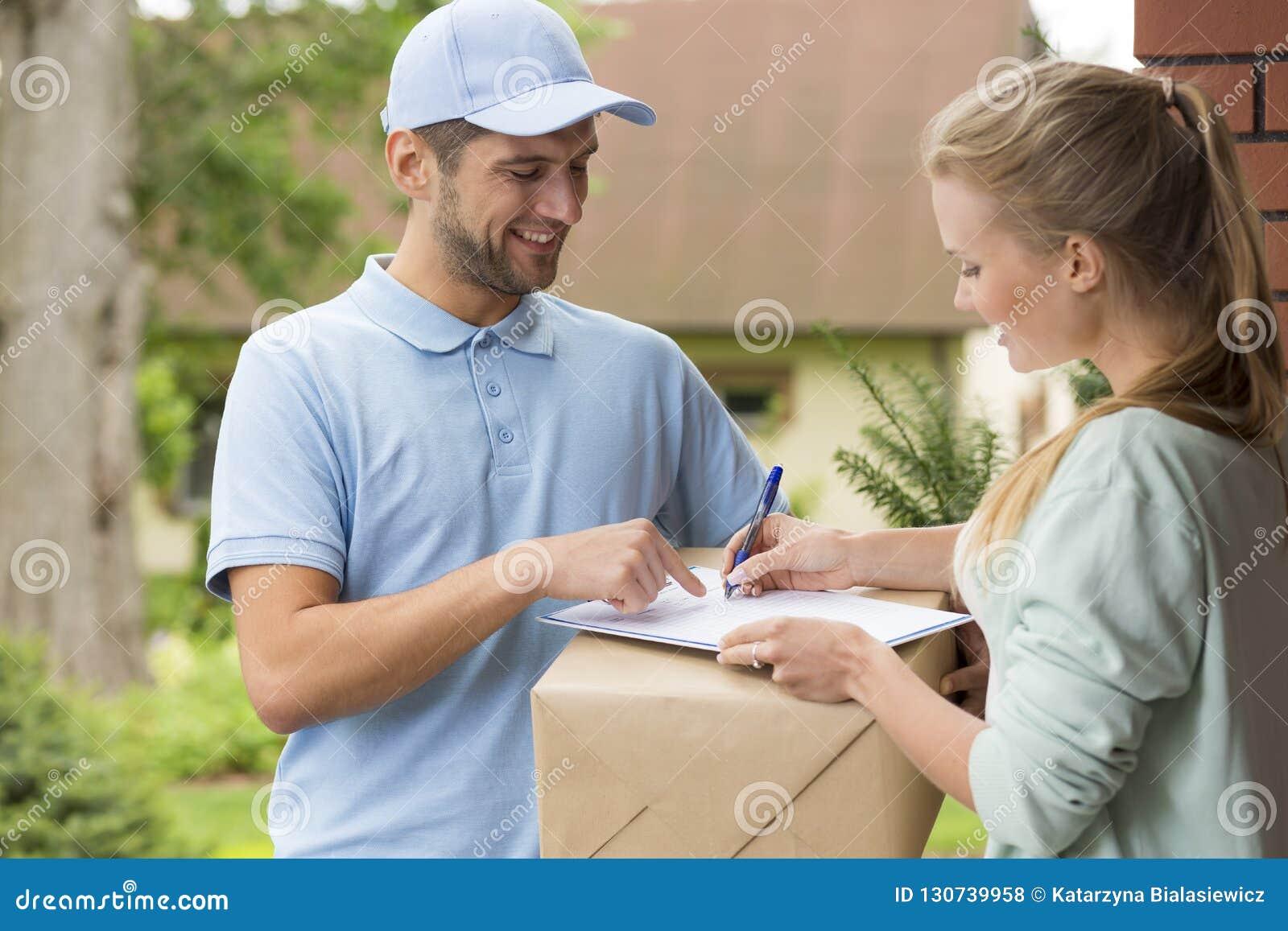 Kurir i blått undertecknande kvitto för likformig och för kvinna av packeleveransen