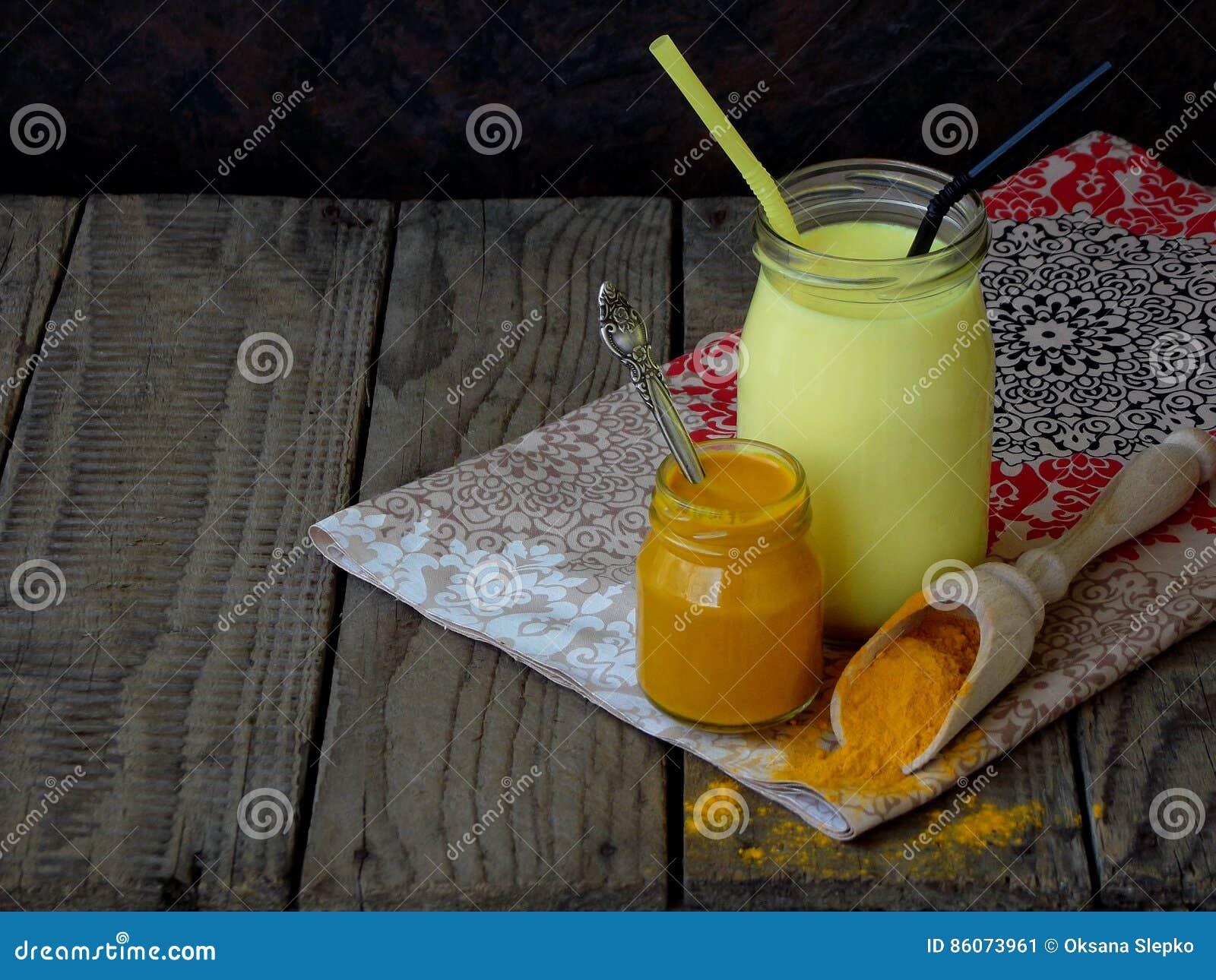 Kurkumapoeder, deeg en latte op houten achtergrond Ayurvedic gezonde gouden drank met kokosmelk en ghee voor schoonheid