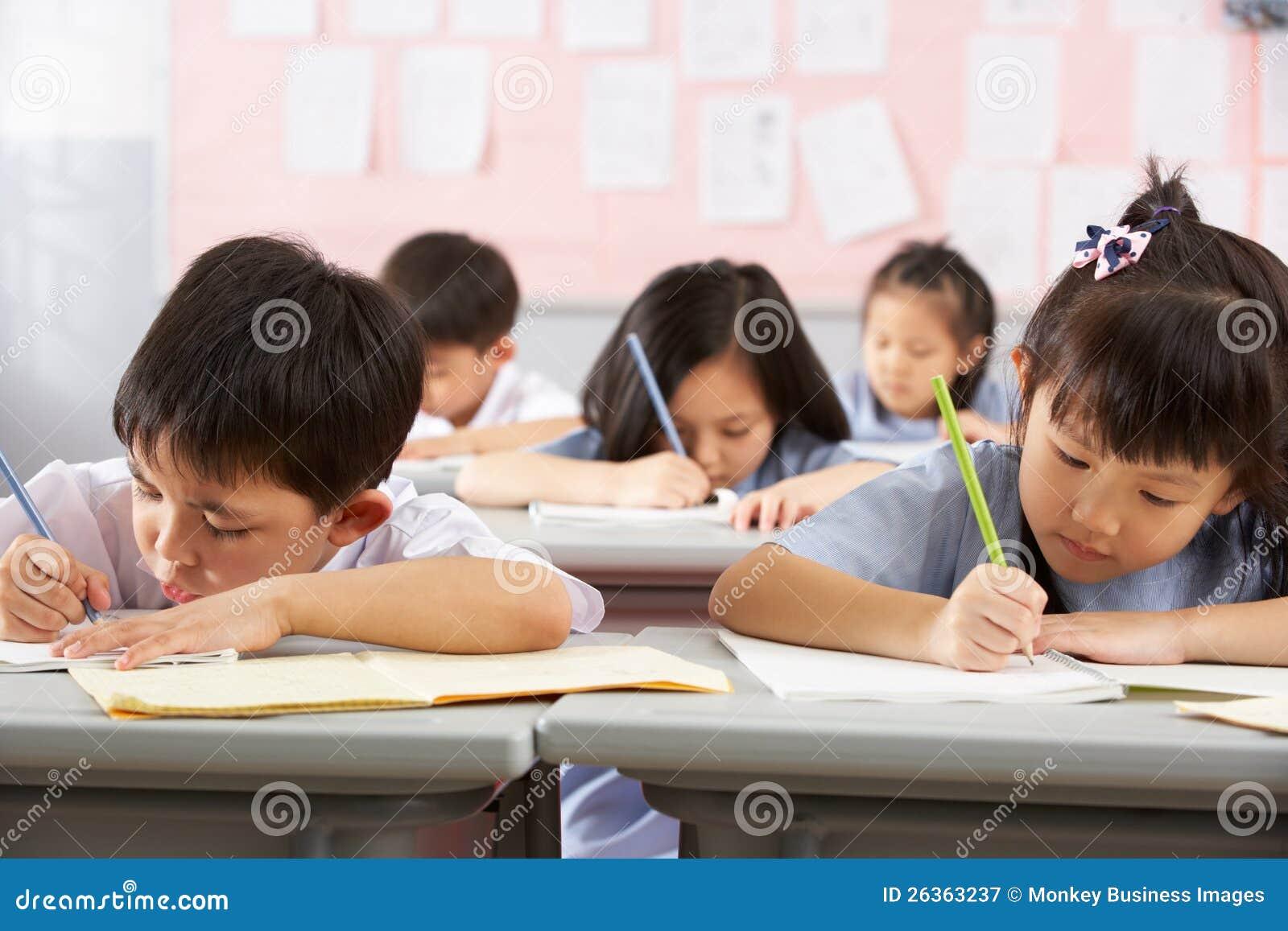 Kursteilnehmer, die an den Schreibtischen in der chinesischen Schule arbeiten
