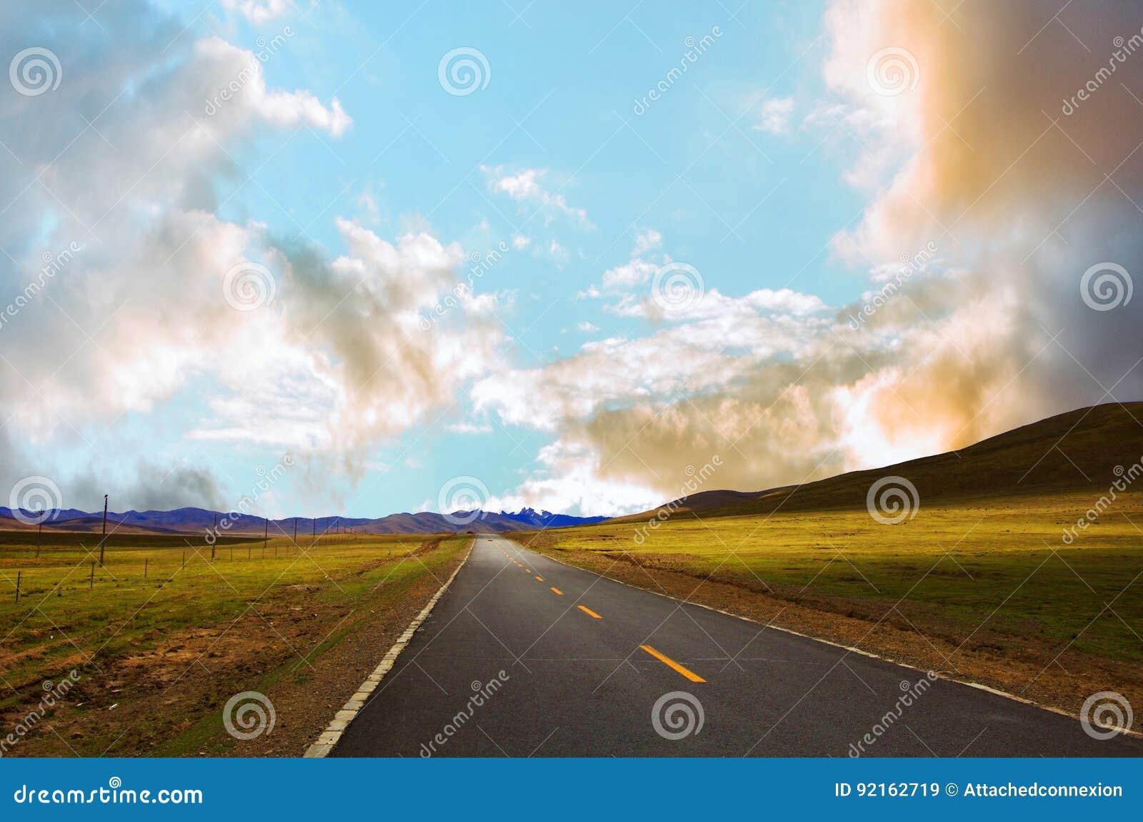 Kurvenreiche Straße entlang den grünen Wiesen