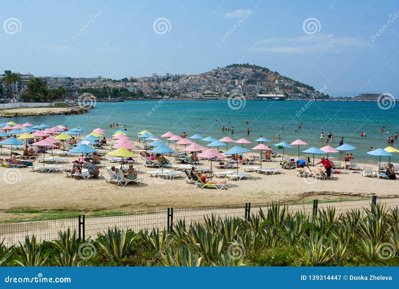 KUSADASI, TURKEY - AUGUST 20, 2017: Beautiful sand beach of Kusadasi with colorful straw umbrellas and lounge chairs, Aegean Sea
