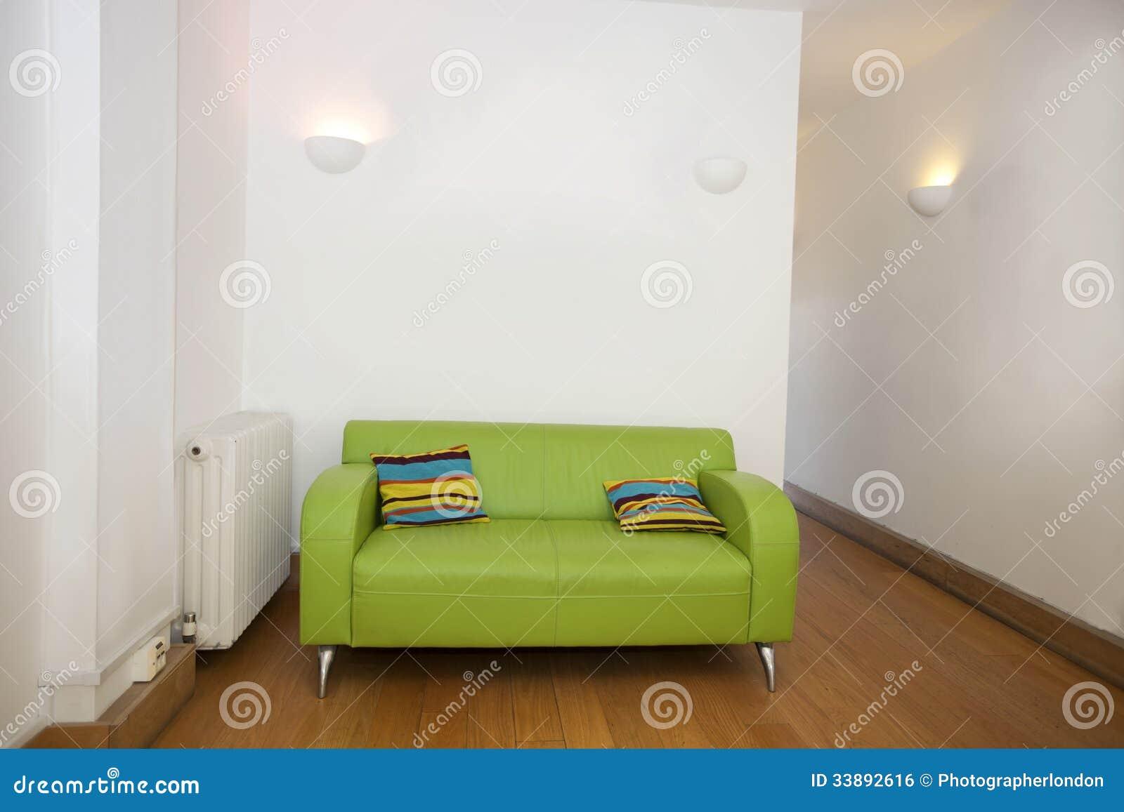 Kussens op groene bank in leeg bureau