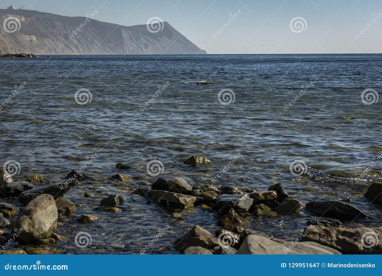 Kust av Blacket Sea på solnedgången Havet stenar och vaggar av olika format och texturer