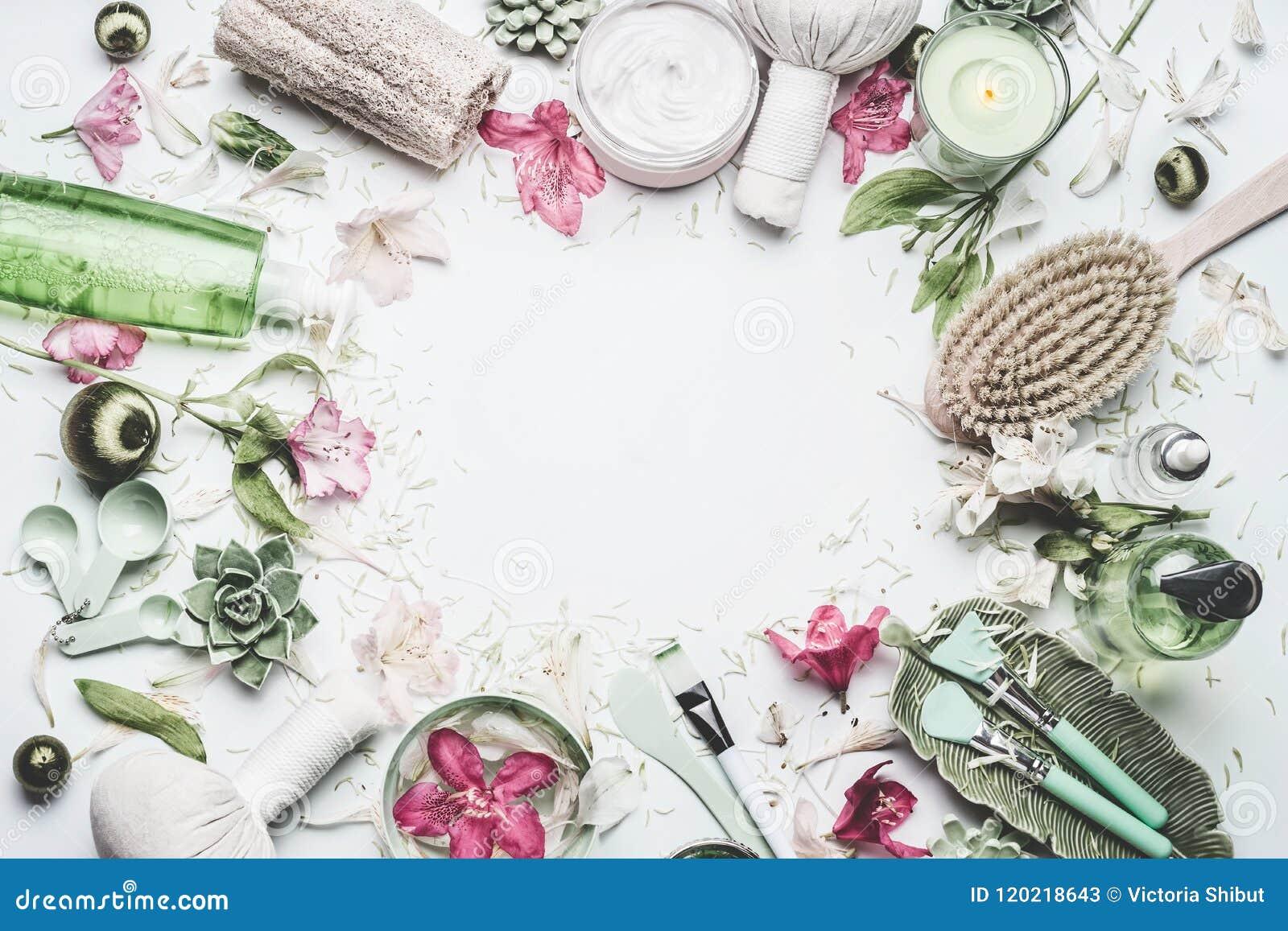 Kuuroord en wellnessachtergrond met bloemen, huidcosmetischee producten en anderen lichaamsverzorging en massagetoebehoren op wit