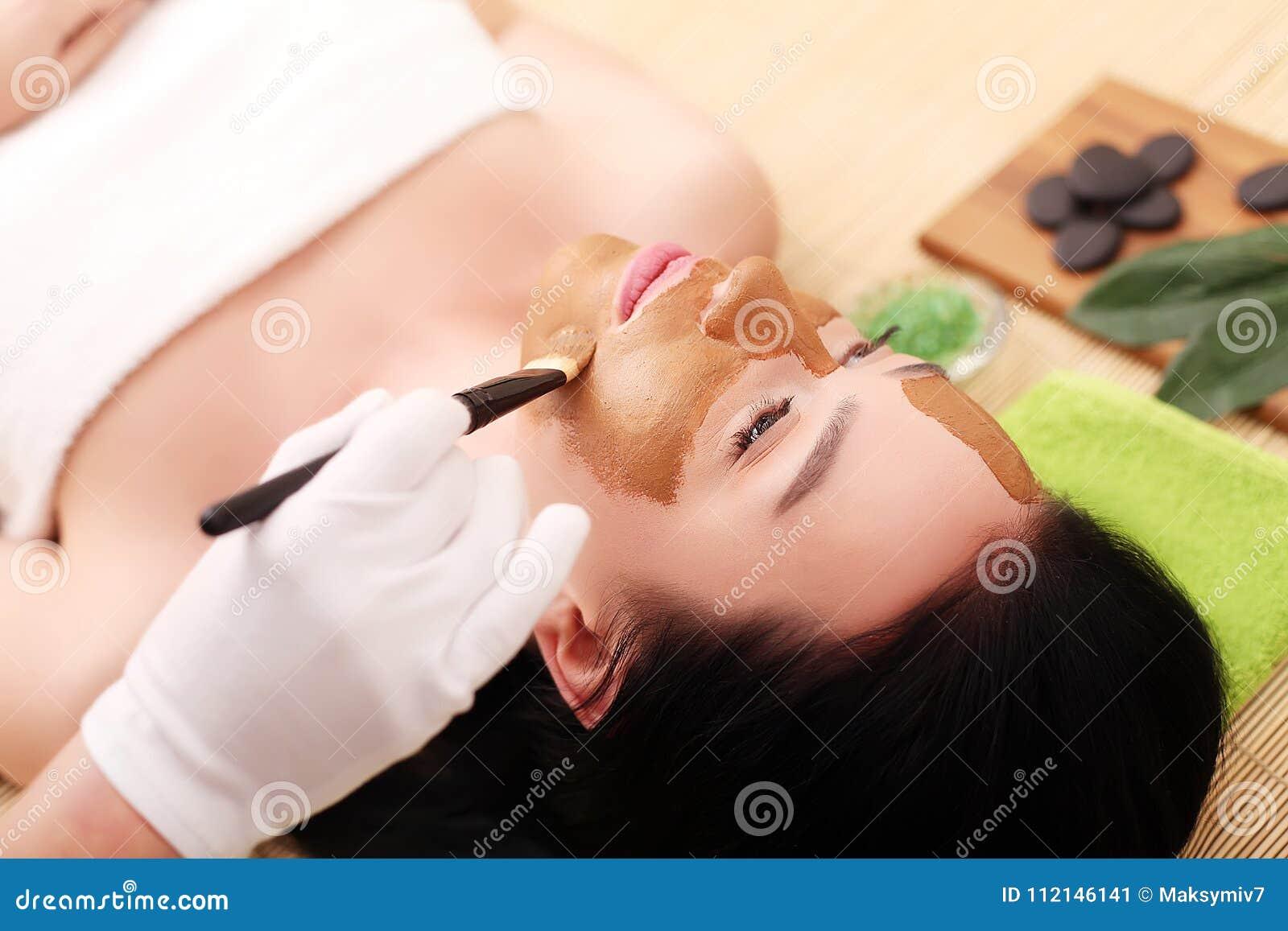 Kuuroordtherapie voor jonge vrouw die gezichtsmasker hebben bij schoonheidssalon - binnen