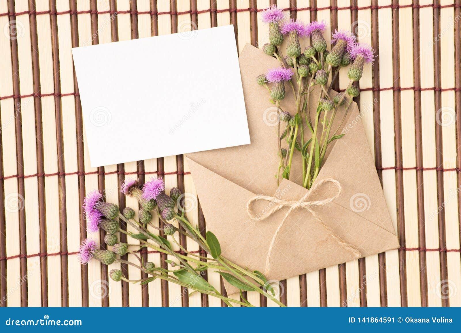 Kuvert av kraft papper med ett tomt meddelande och med härliga blommor