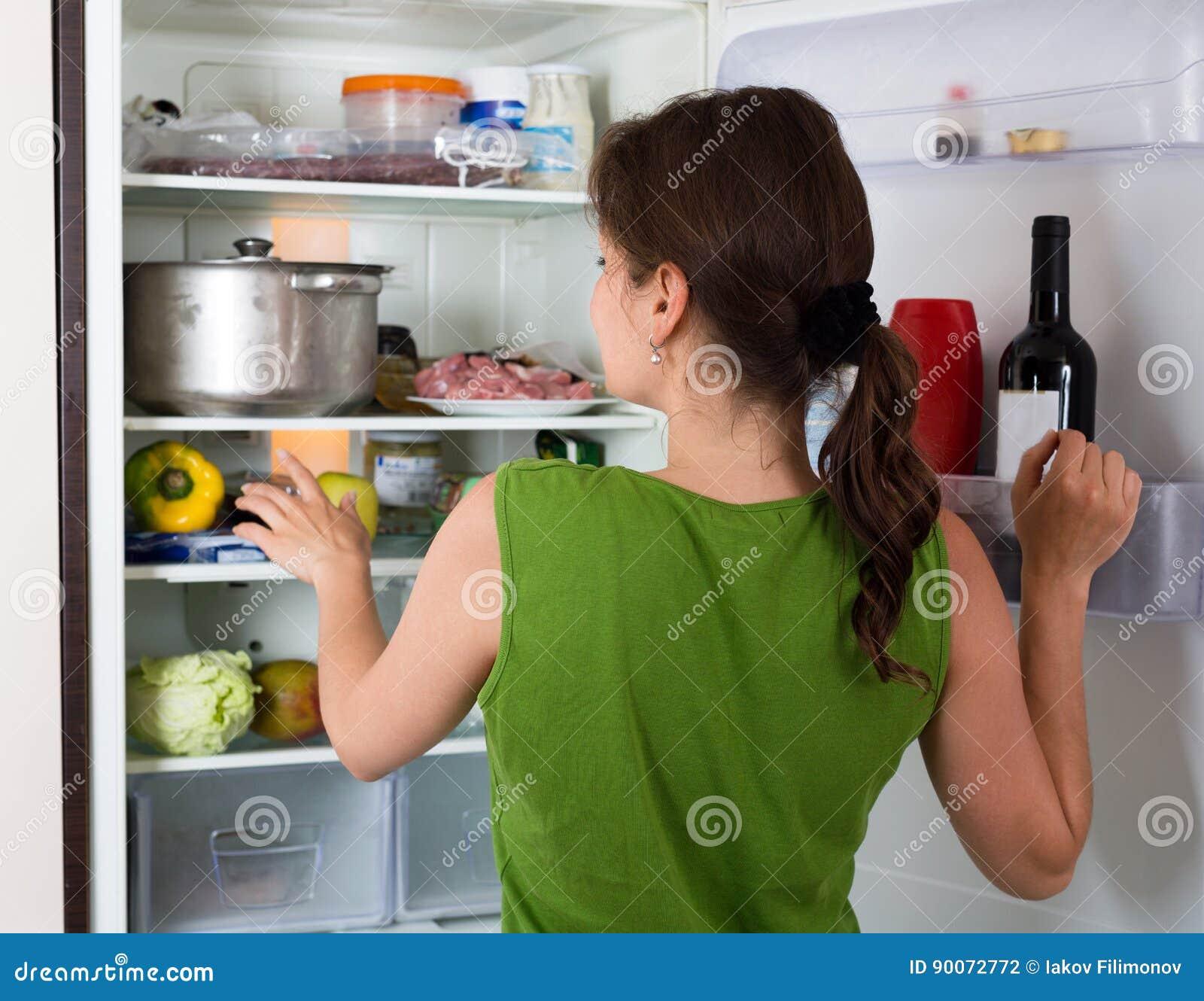Kvinnaöppningskylskåp med mat