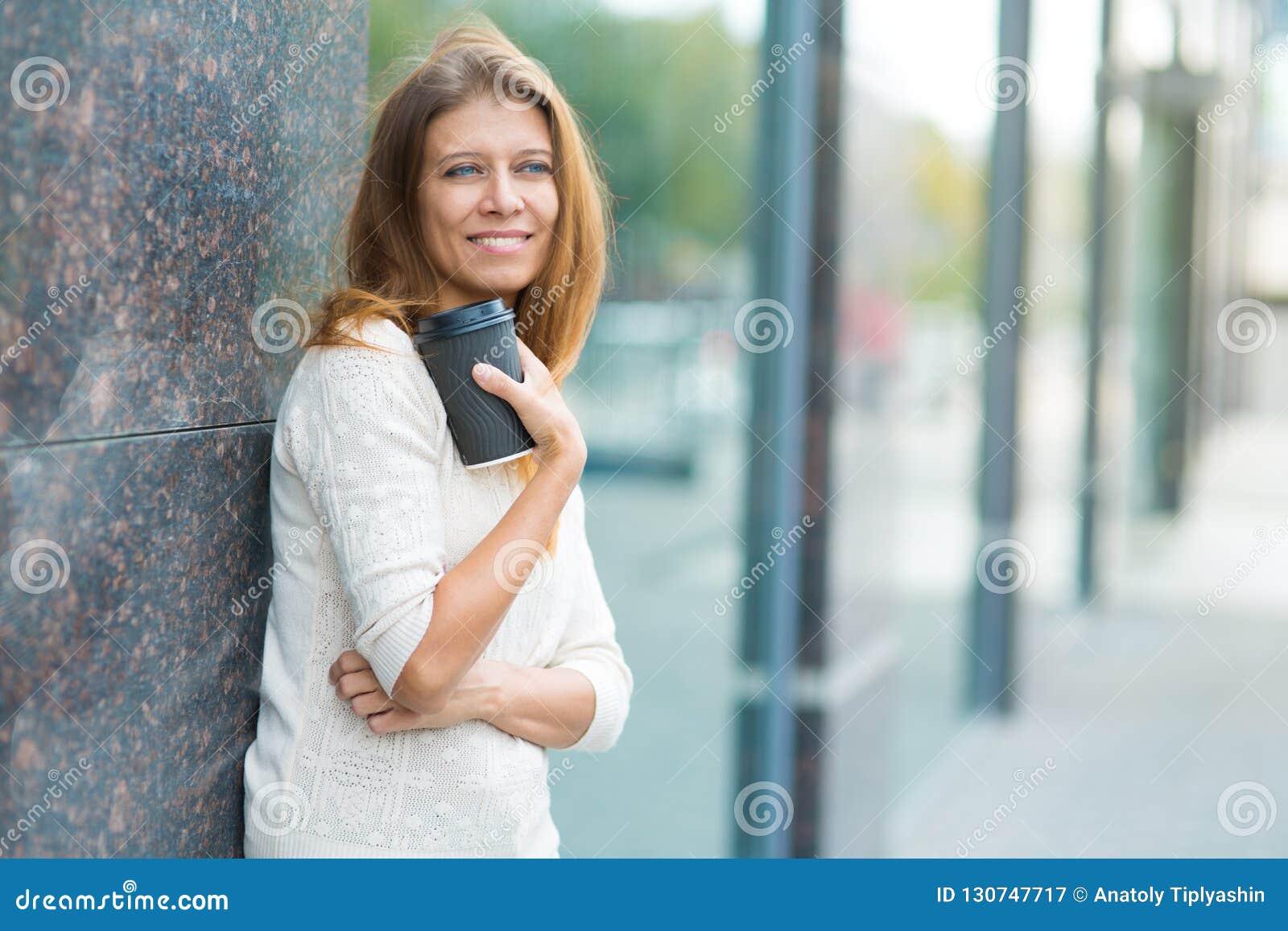 Kvinna 30 år gammalt gå i staden på en solig dag