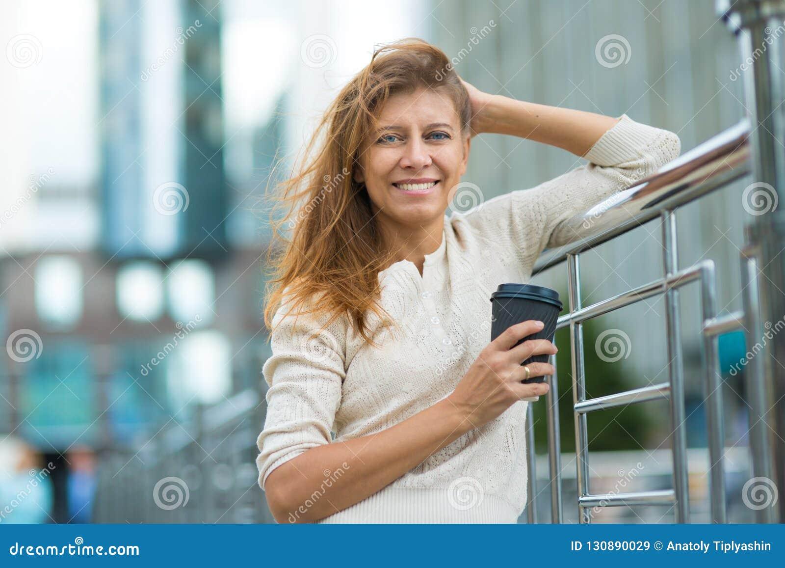 Kvinna 30 år gammalt gå i staden på en solig dag med en kopp