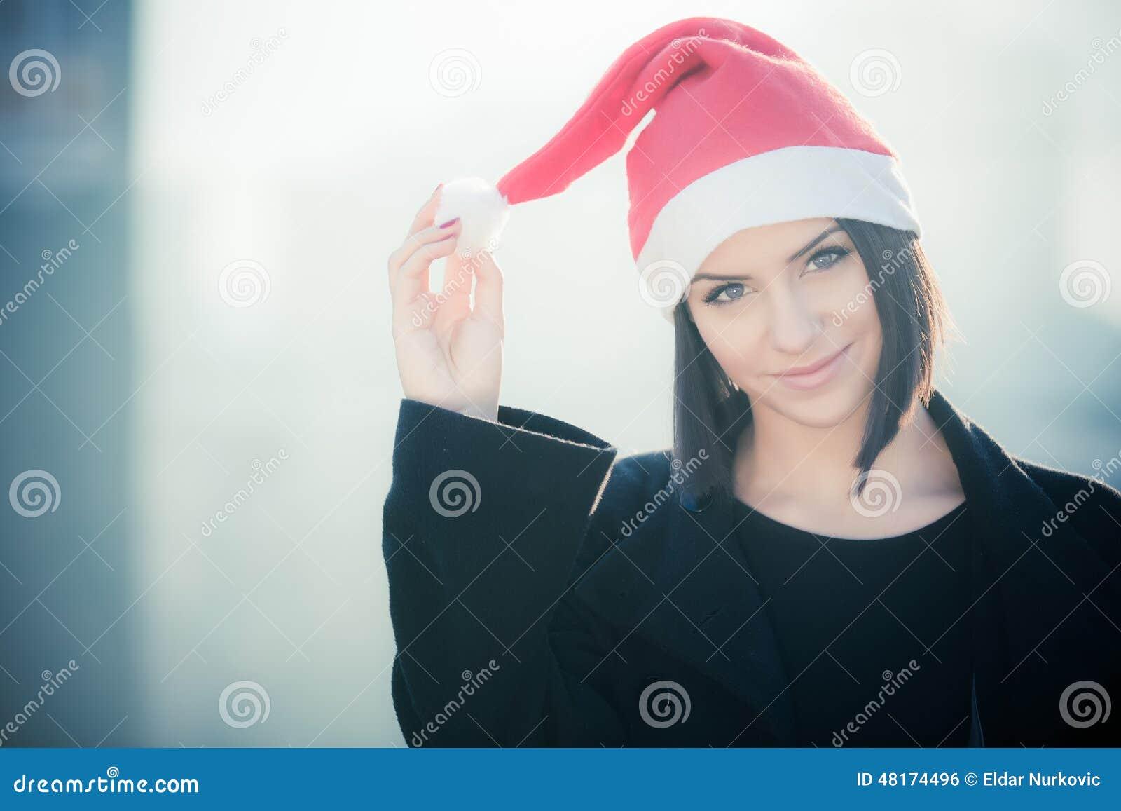 Kvinna för juljultomtenhatt som utomhus ler ståenden Le den lyckliga flickan som bär hennes jultomtenhatt med stads- bakgrund för