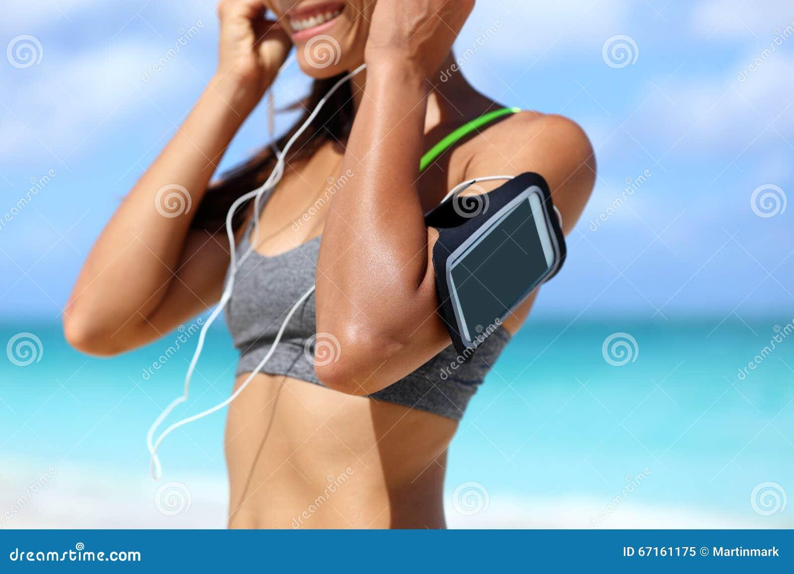 Kvinna för konditiontelefonarmbindel som sätter hörlurar
