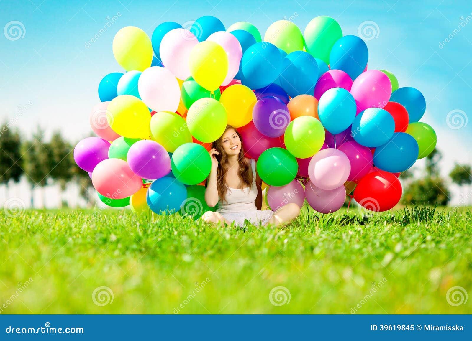 Kvinna för lycklig födelsedag mot himlen med regnbåge-färgade luftlodisar