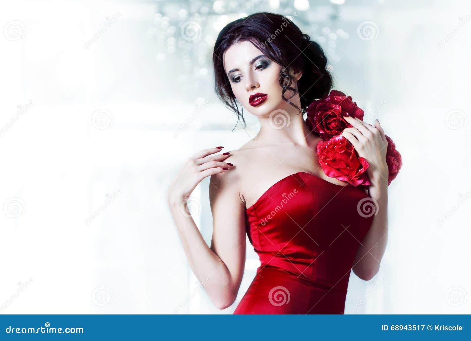 Kvinna för skönhetbrunettmodell i röd klänning för afton Makeup och frisyr för härligt mode lyxig, på bakgrunden av