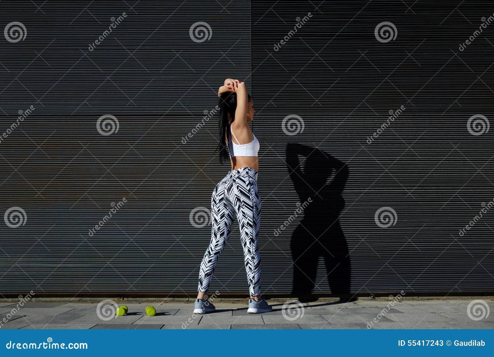 Kvinna för stående för bakre sikt sportig med det perfekta diagramet och bakdelar som sträcker hennes armar mot väggen med kopier