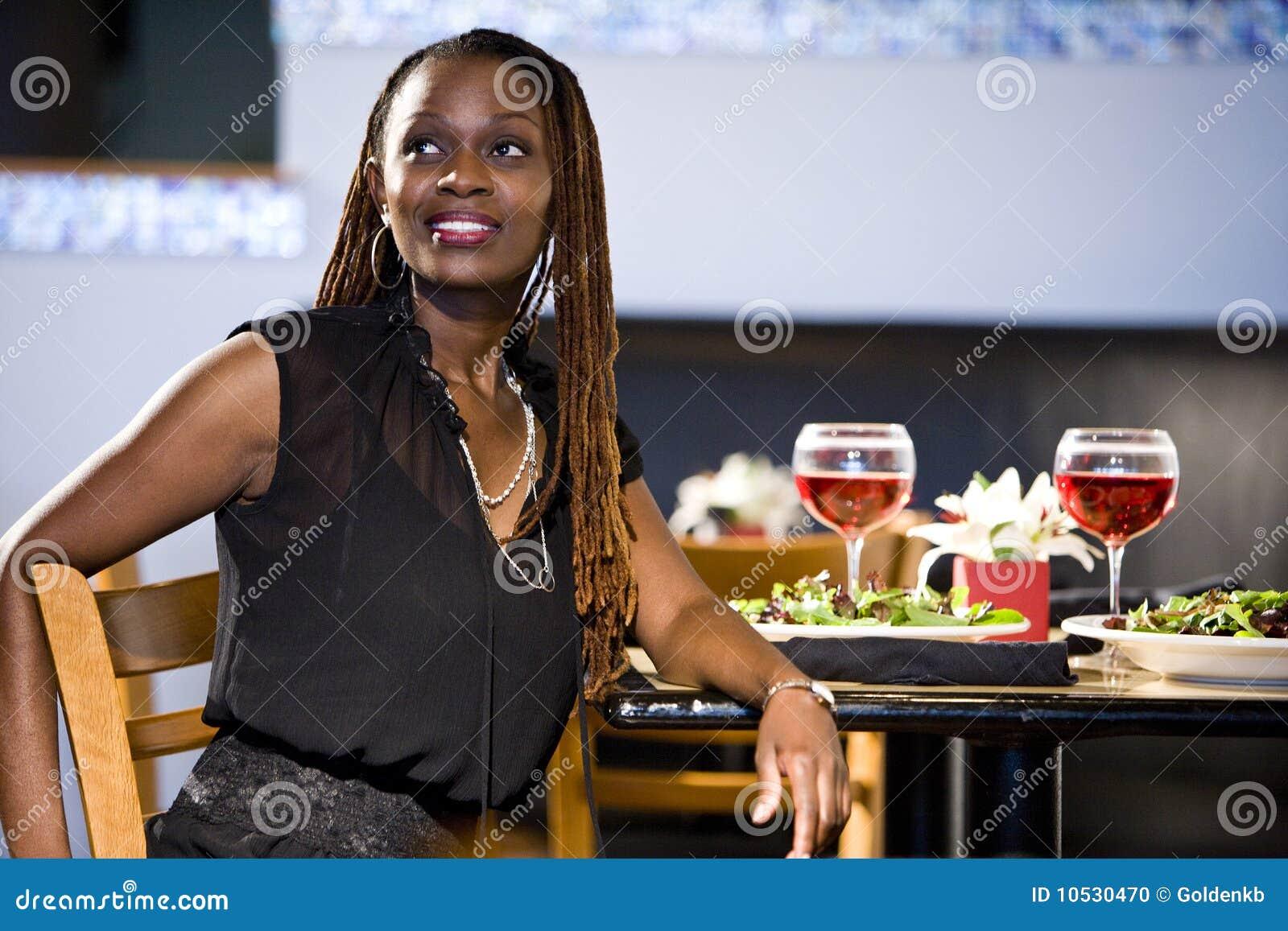 Kvinna för tabell för afrikansk amerikanrestaurang sittande