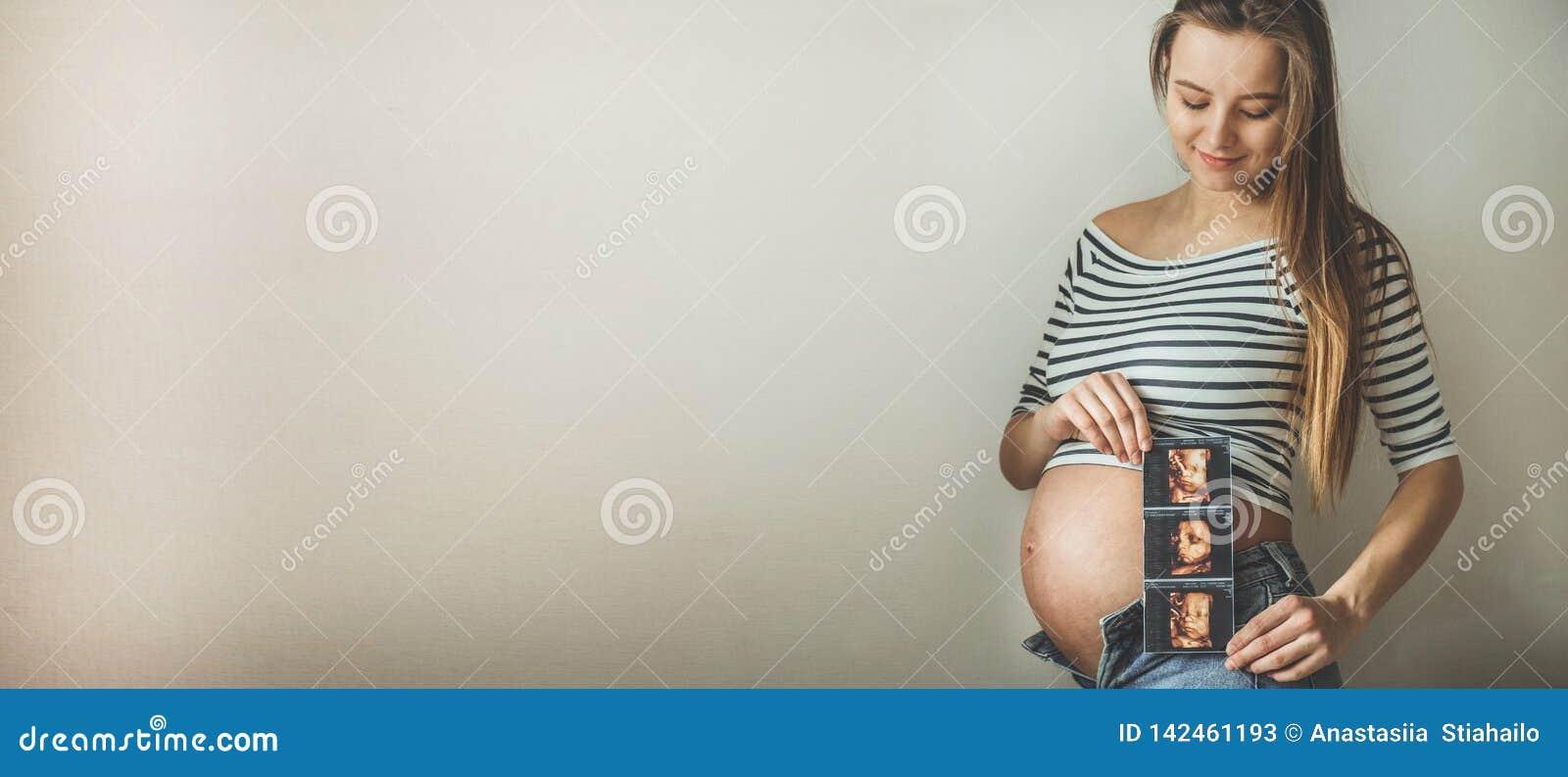 Kvinna för ultrasound för holdingbild gravid