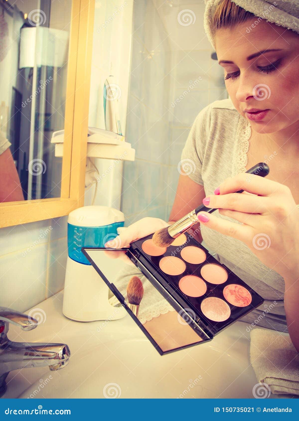 Kvinna i badrummet som applicerar konturbronzer p? borste