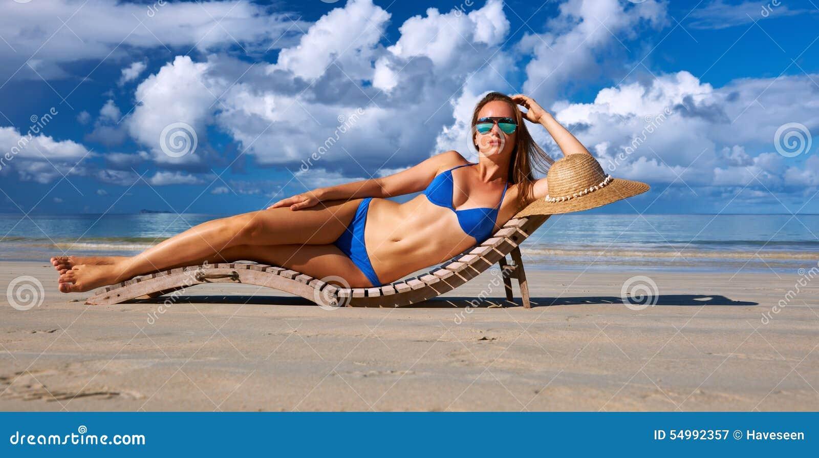 Kvinna i bikinin som ligger på stranden på Seychellerna