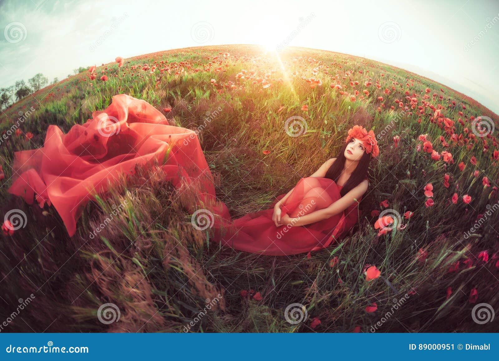 Kvinna i blommavallmofält i sommar
