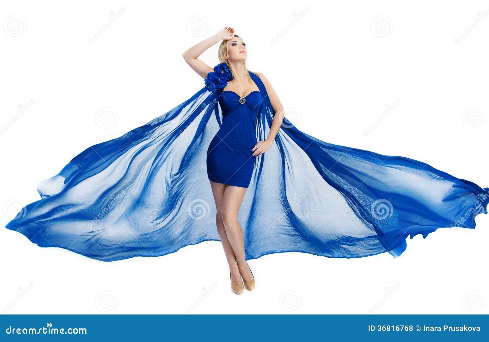 Kvinna i den blåa fladdraklänningen som vinkar på vind över vit