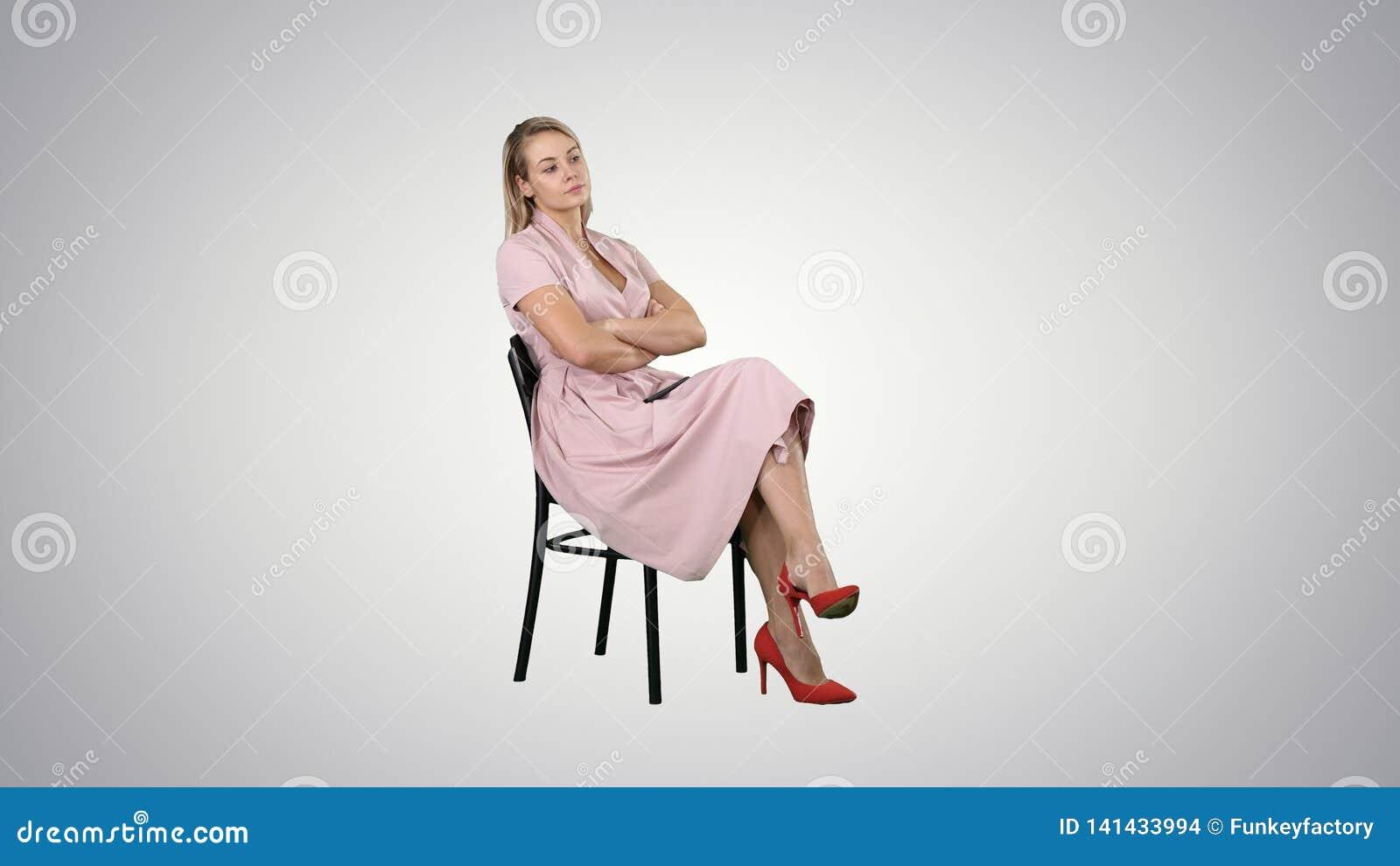 Kvinna i den rosa klänningen som sitter på en stol som väntar på någon på lutningbakgrund