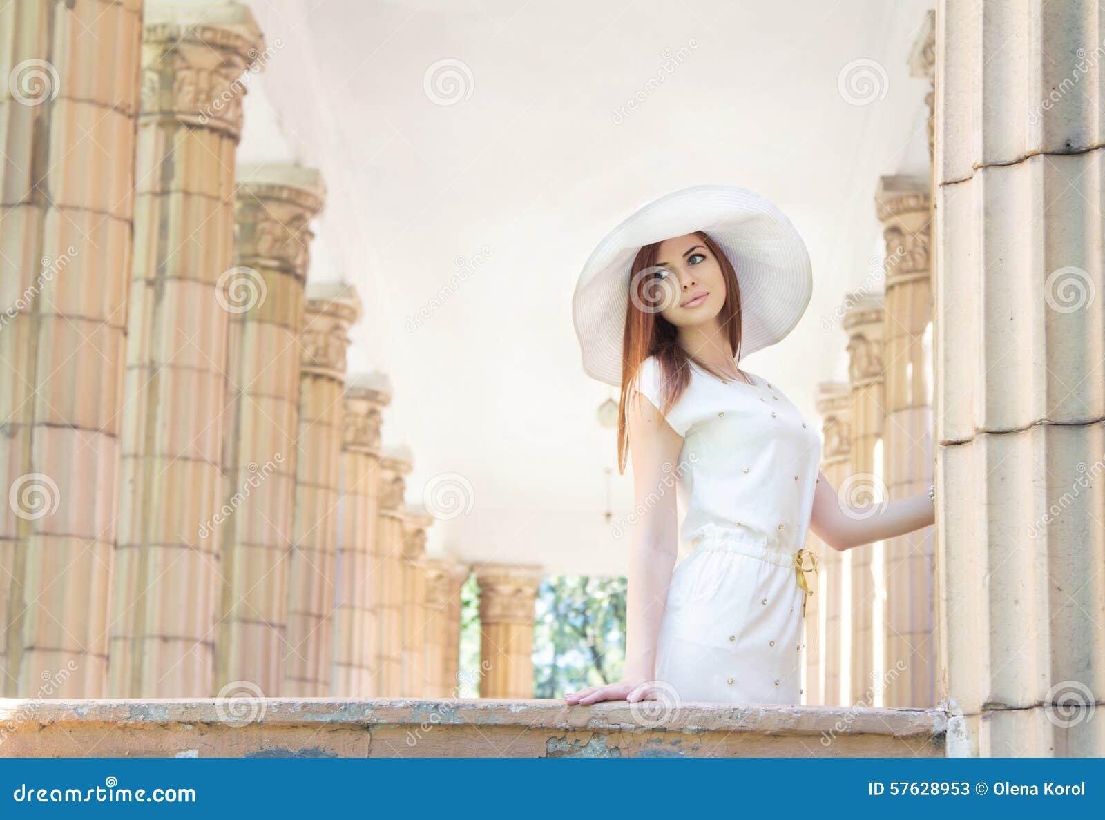 Kvinna i den vita hatten mellan kolonner
